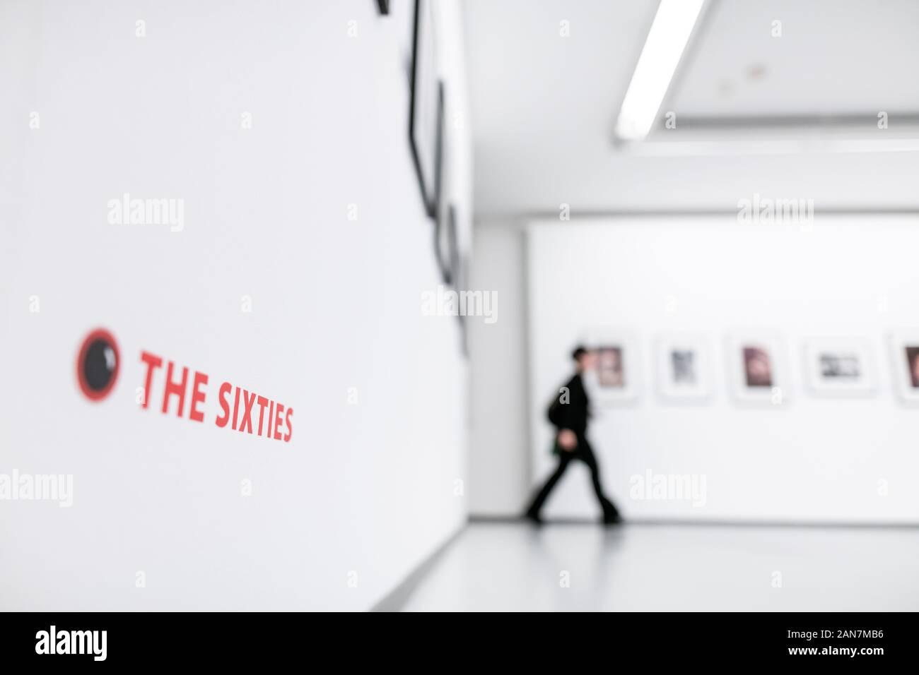 """Oberhausen, Germania. 16 gennaio, 2020. 'L'Sixties' sorge su una parete mentre un visitatore in background passeggiate attraverso la mostra. Premere il tasto Conferenza per la mostra 'fotografo tra musicisti: Linda McCartney - Anni Sessanta e più"""". Sul display sono le foto da Linda McCartney dalla scena della musica alla fine degli anni sessanta: Janis Joplin, Jimi Hendrix, Aretha Franklin, i Beatles e i Rolling Stones e altri. In aggiunta, la mostra è dedicata ai lavori stradali come McCartney il contributo al cosiddetto street photography. Sul display sono 180 opere. Credito: Fabian Strauch/dpa/Alamy Live News Foto Stock"""
