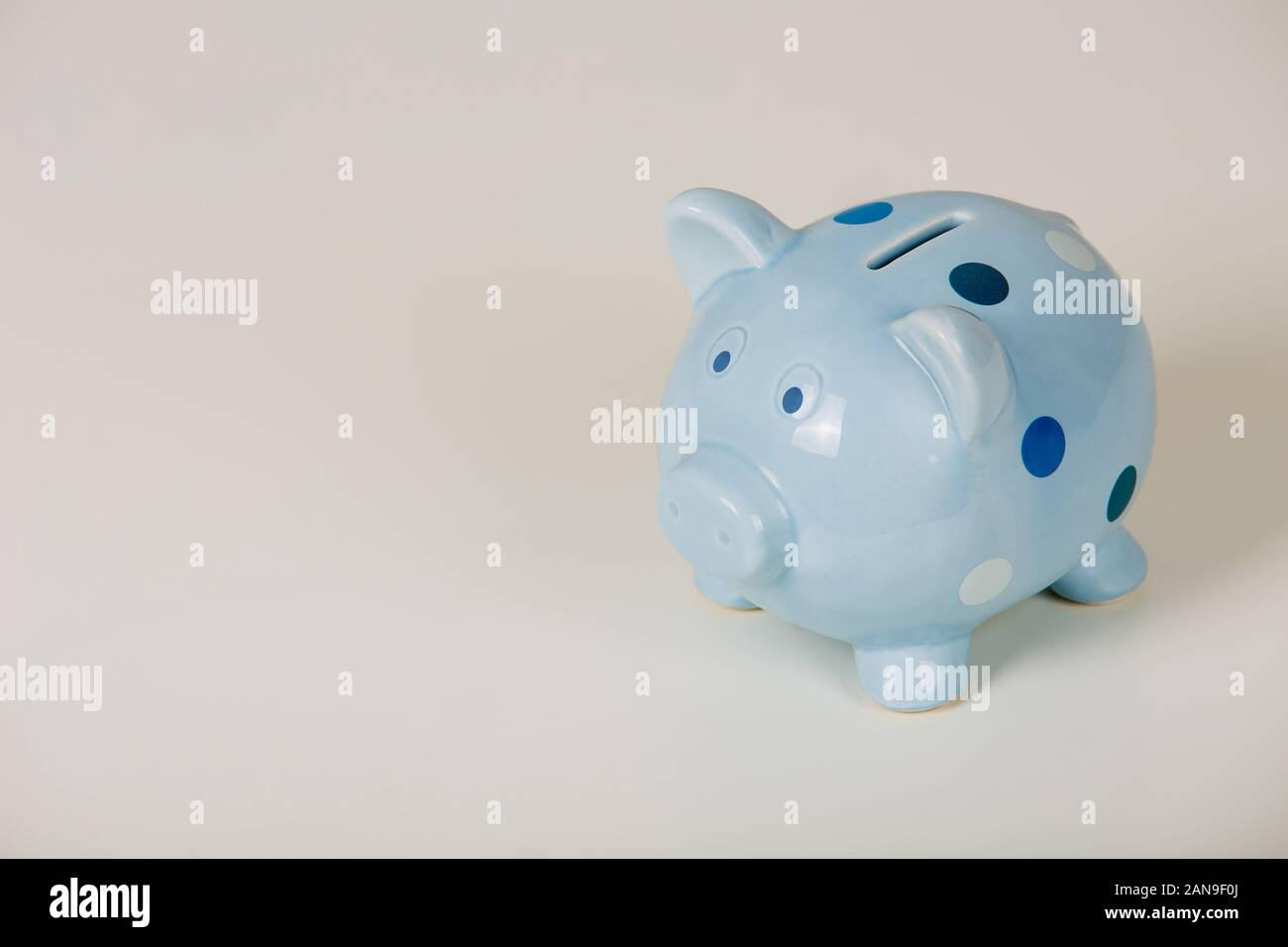 Close up di blu salvadanaio isolate su uno sfondo grigio con copia spazio. Finanza e denaro simbolo, il concetto di risparmio. Foto Stock