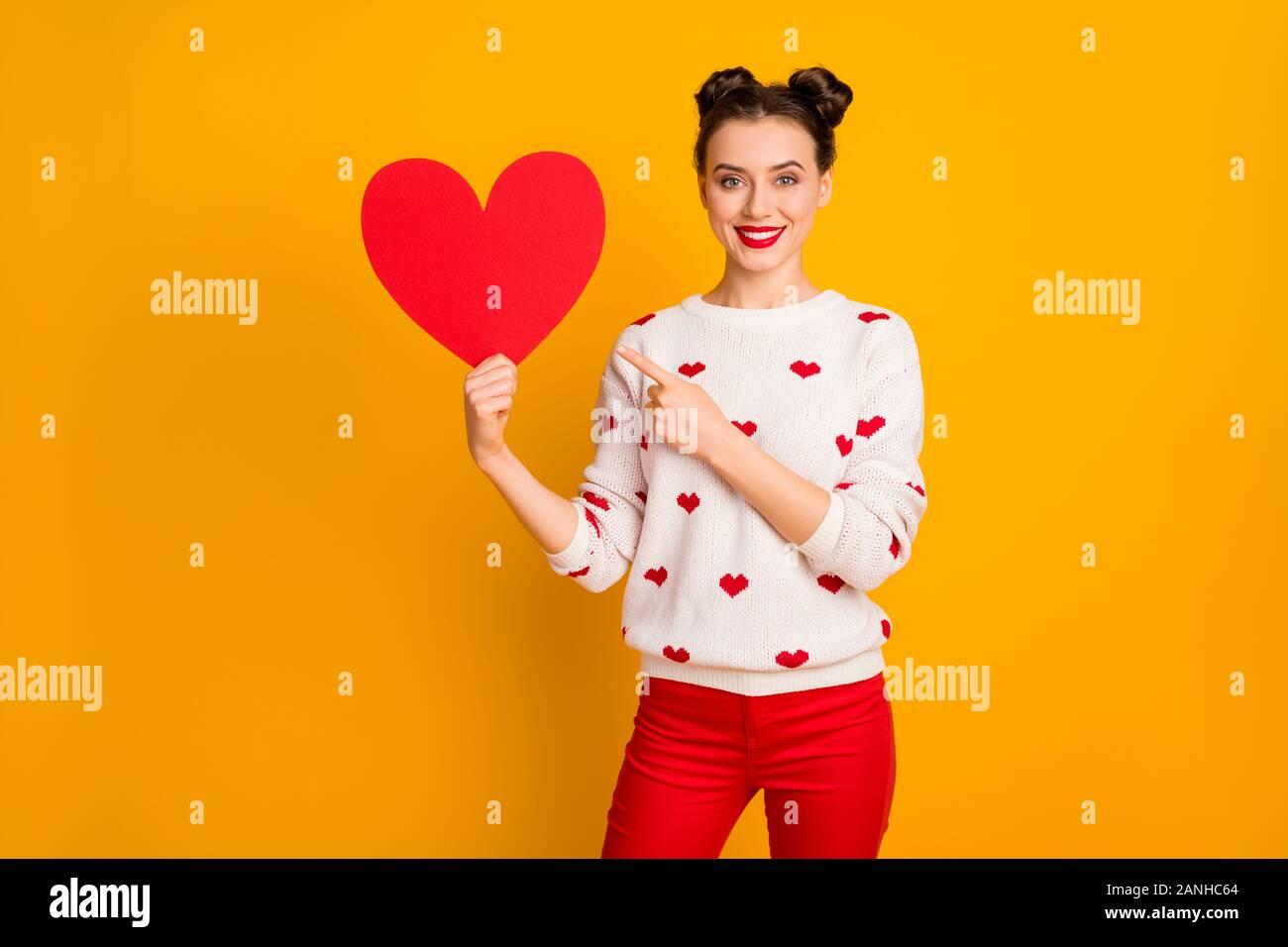 Foto di abbastanza affettuoso lady tenere la carta cuore mostra data cartolina indicando il dito promozione usura rosso bianco cuori pattern pullover pantaloni Foto Stock