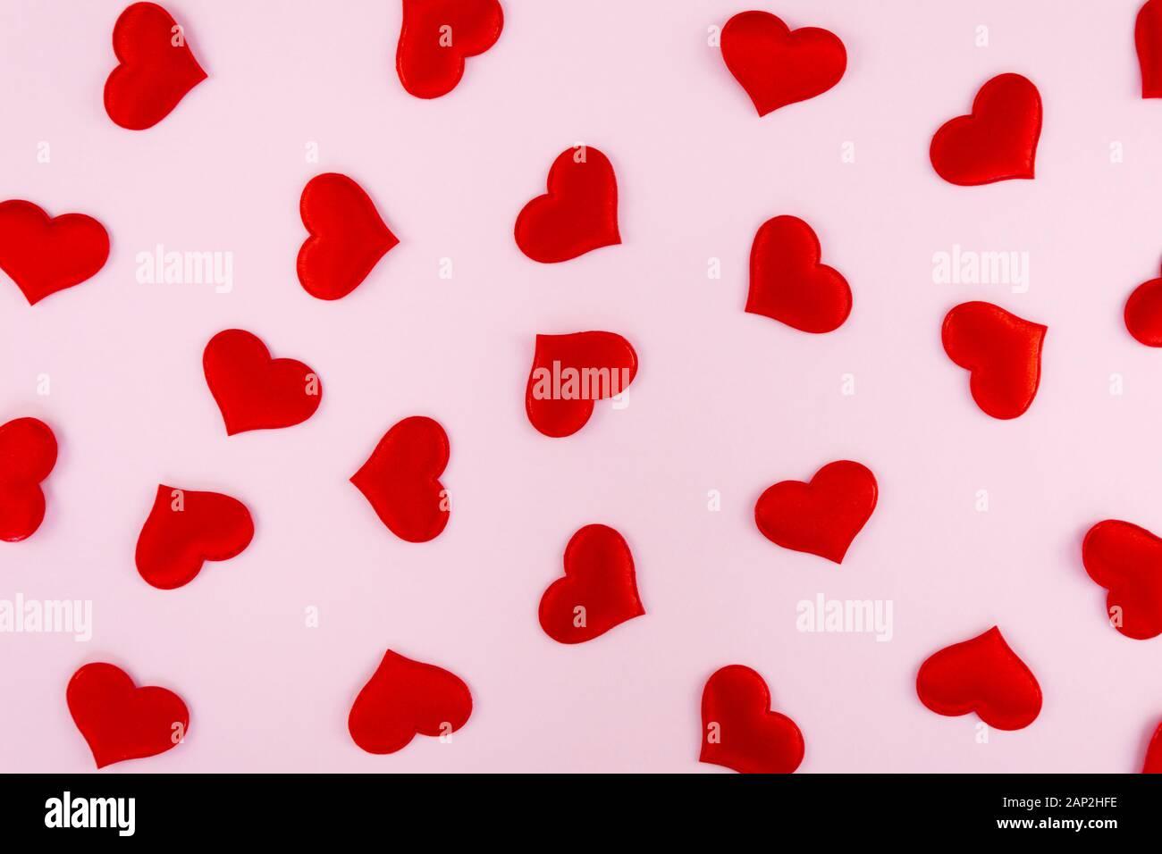 Cuori rossi sparsi su un sfondo rosa con spazio libero per il testo Foto Stock