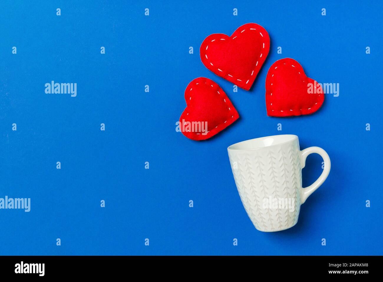 Vista dall'alto composizione di cuori rossi che cadono da una tazza su sfondo colorato con spazio di copia. Concetto di relazione romantica. San Valentino. Foto Stock