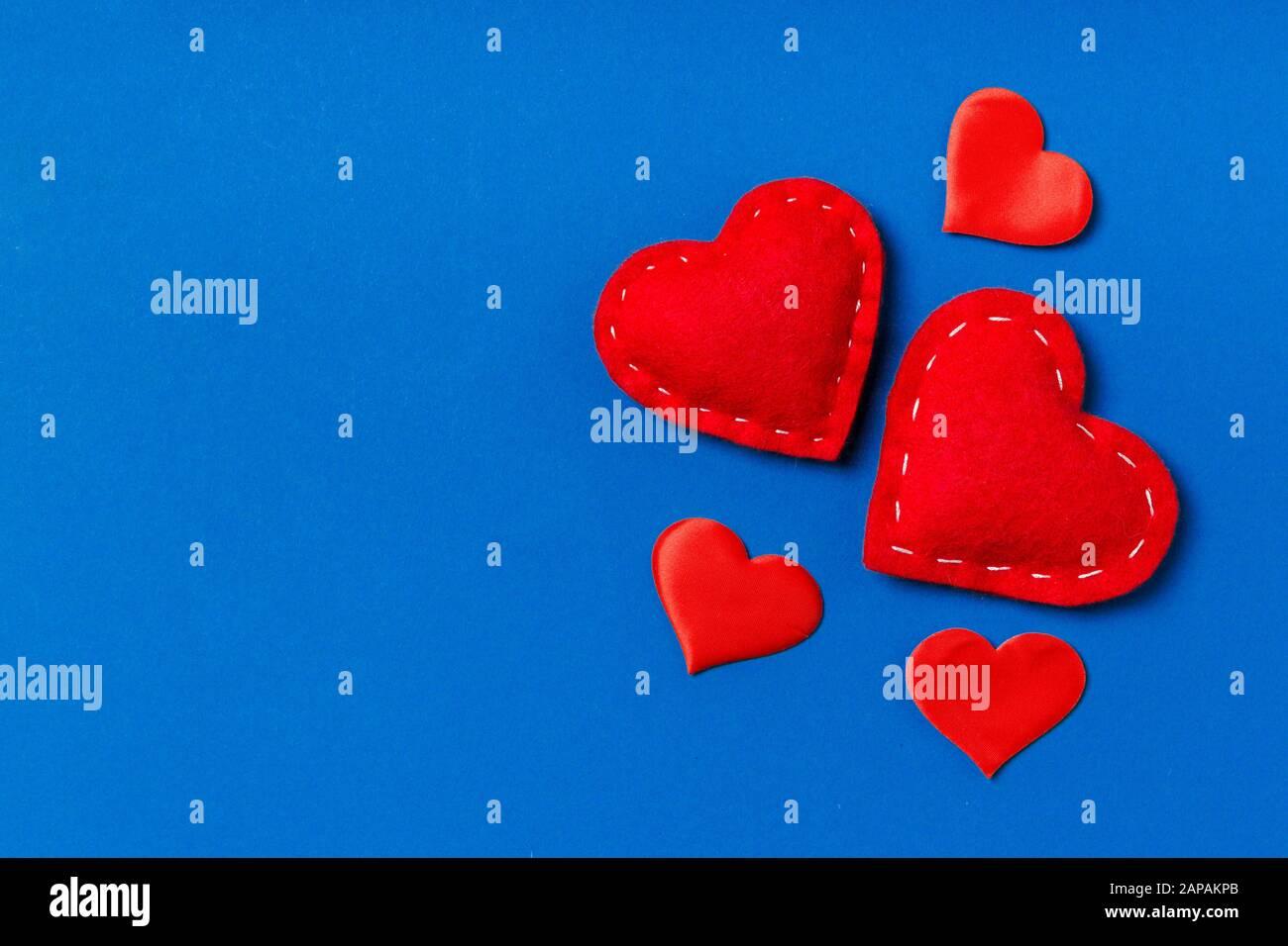 Vista dall'alto composizione dei cuori rossi su sfondo colorato. Concetto di relazione romantica. Il giorno di Valentaine. Foto Stock