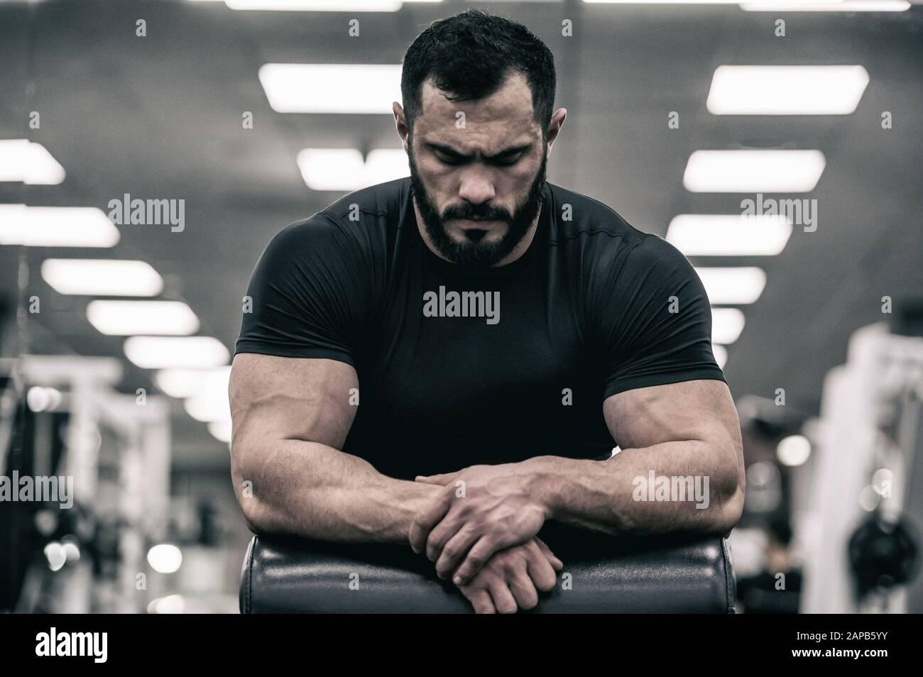 mente mentale sport motivazione concetto di giovane uomo forte con la barba che indossa la maglia nera concentrazione relax in palestra sport Foto Stock