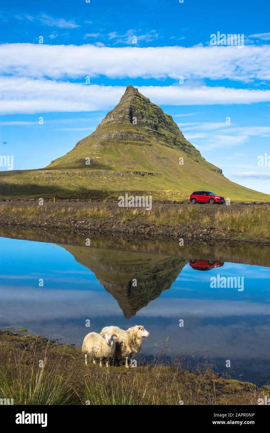 Estate tramonto sulla famosa cascata Kirkjufellsfoss con Kirkjufell mountain in background in Islanda. Lunga esposizione. Foto Stock