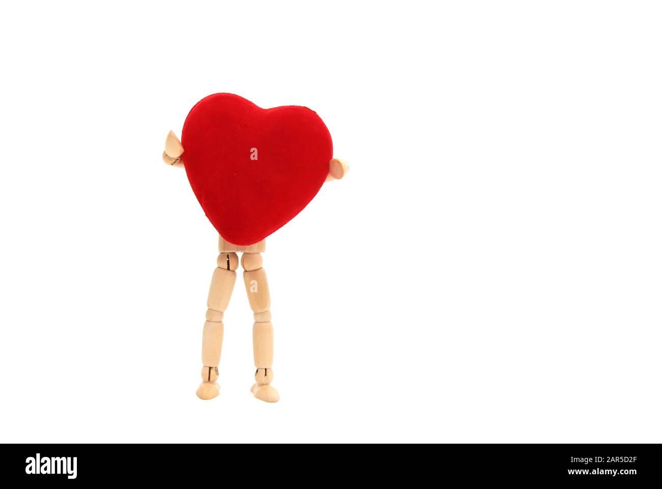 Una bambola di legno che tiene un cuore su uno sfondo bianco Foto Stock