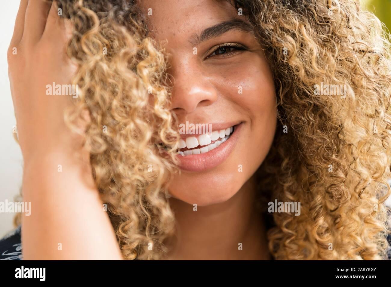 Donna sorridente di toccare i capelli Foto Stock