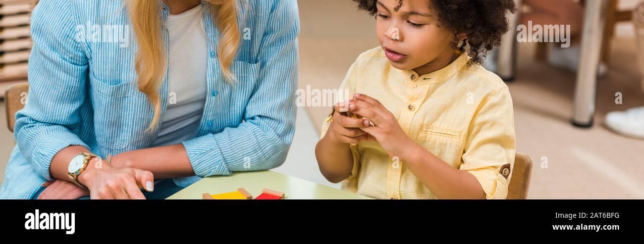 Scatto panoramico del capretto americano africano che gioca il gioco educativo dall'insegnante nella scuola di montessori Foto Stock