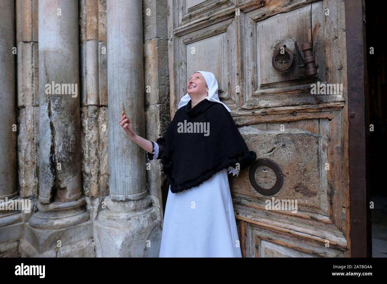 Un pellegrino ortodosso russo che prende il selfie all'ingresso della Chiesa del Santo Sepolcro nel quartiere cristiano della città vecchia Gerusalemme Est Israele Foto Stock