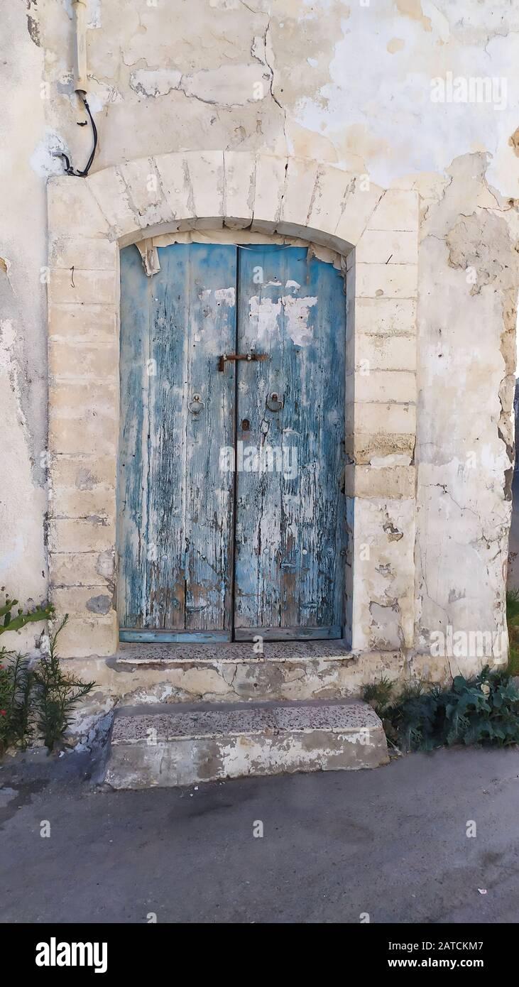 Tradizionale porta dipinta molto vecchia in un quartiere storico o medina, Tunisia. Immagine colorata e testurizzata dell'architettura musulmana. Foto Stock