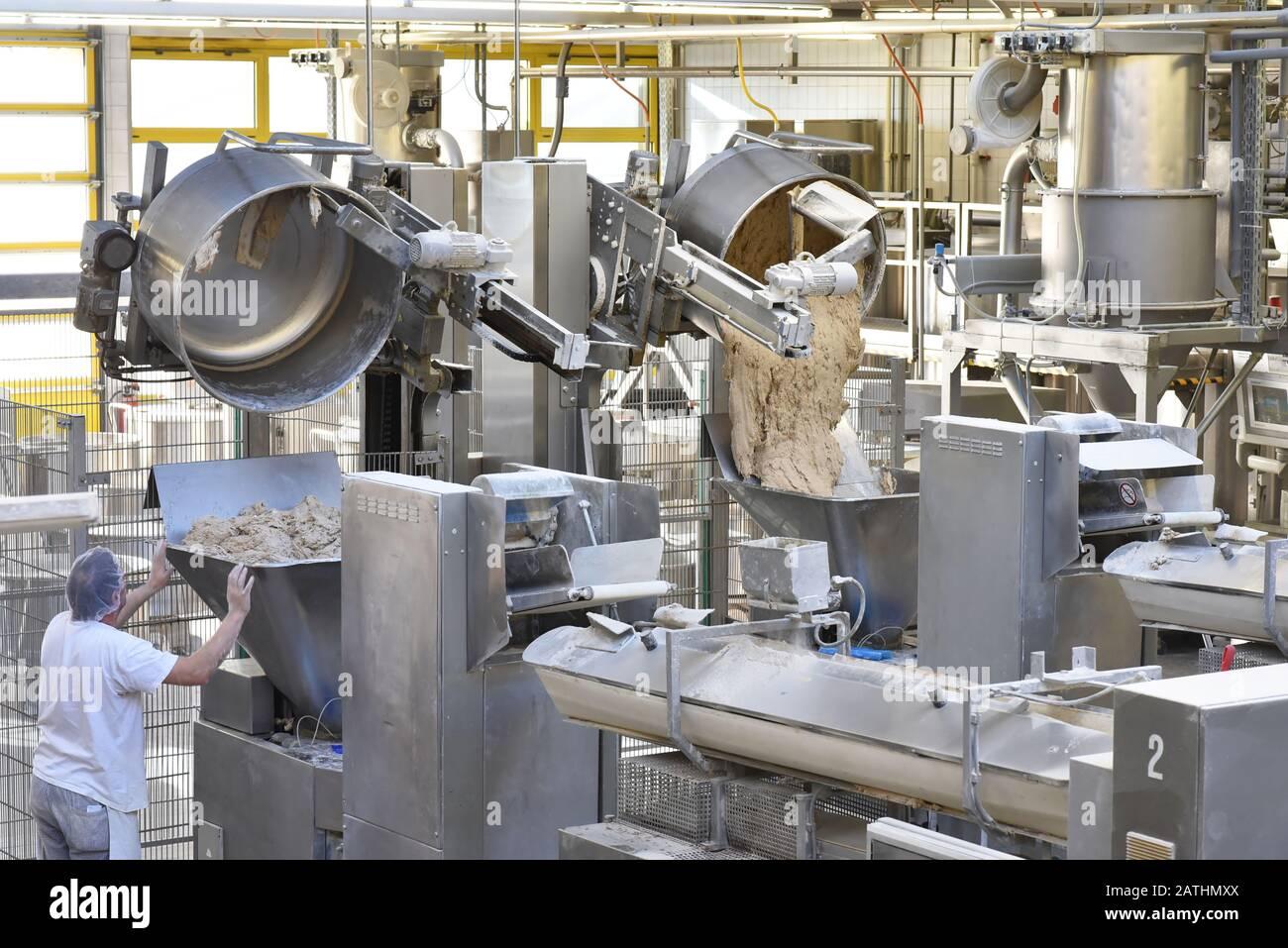 produzione industriale di prodotti da forno su una linea di assemblaggio - tecnologia e macchinari nella fabbrica alimentare Foto Stock