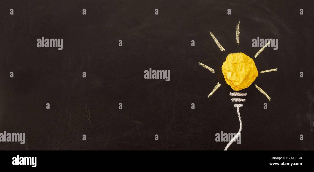 Nuova idea creativa. Innovazione, brainstorming, ispirazione e concetti di soluzione. Lampadina con carta sbriciolata su sfondo nero. Foto Stock