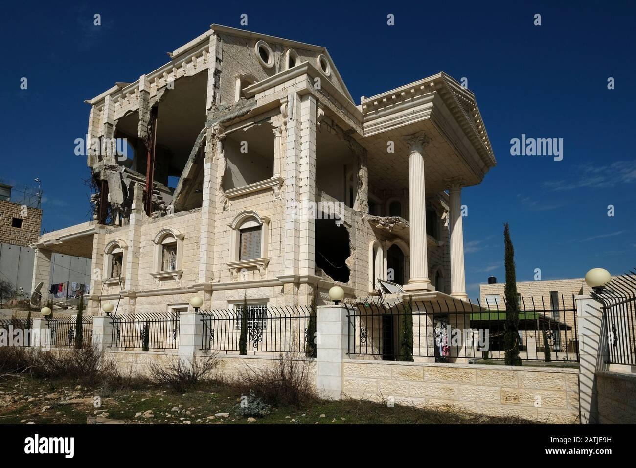Un palazzo i cui piani superiori sono stati demoliti su ordine israeliano perché la sua altezza ha permesso una vista sulla barriera di sicurezza ad Abu Dis o Abu Deis, una comunità palestinese che appartiene al governatorato palestinese di Gerusalemme a sud-est di Gerusalemme in Israele Foto Stock