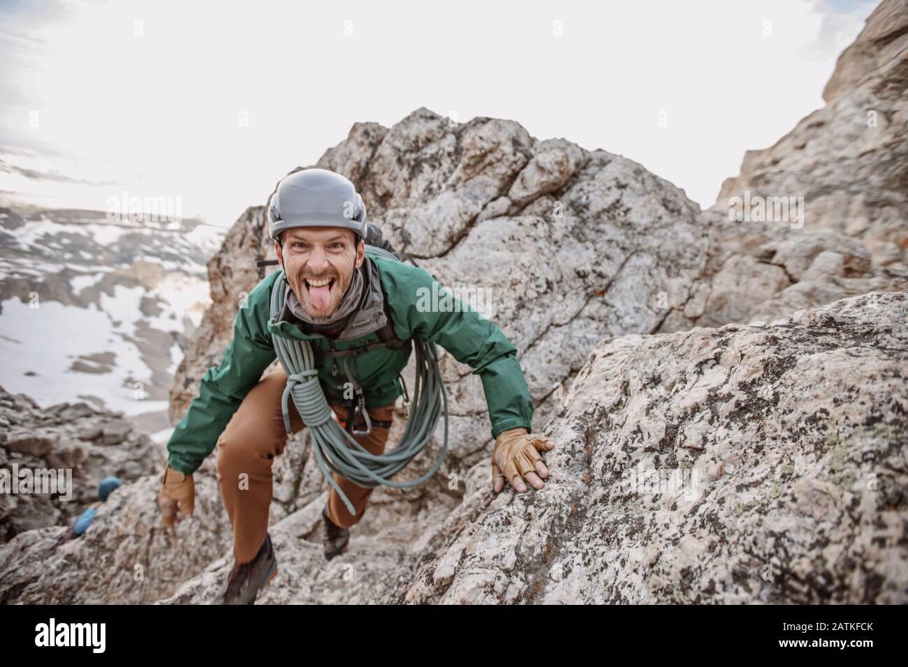 Scalatore di roccia maschio con corda e casco si stacca lingua fuori Foto Stock