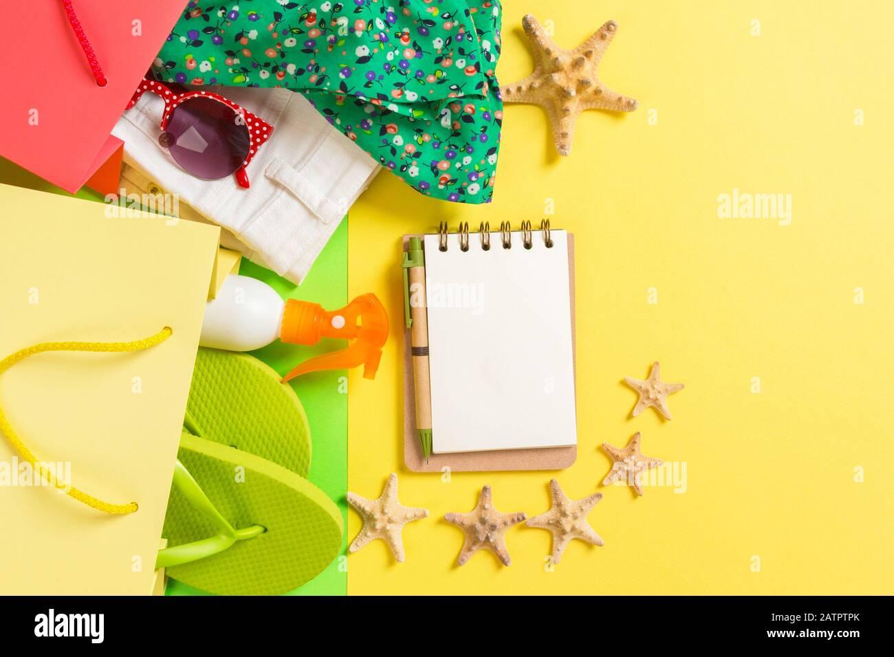 Concetto di estate di colorati negozi sacchi pieni di vestiti. Buste regalo con T-shirt, jeans corti, flip-flop, un notebook e una bottiglia di crema solare. Estate Foto Stock