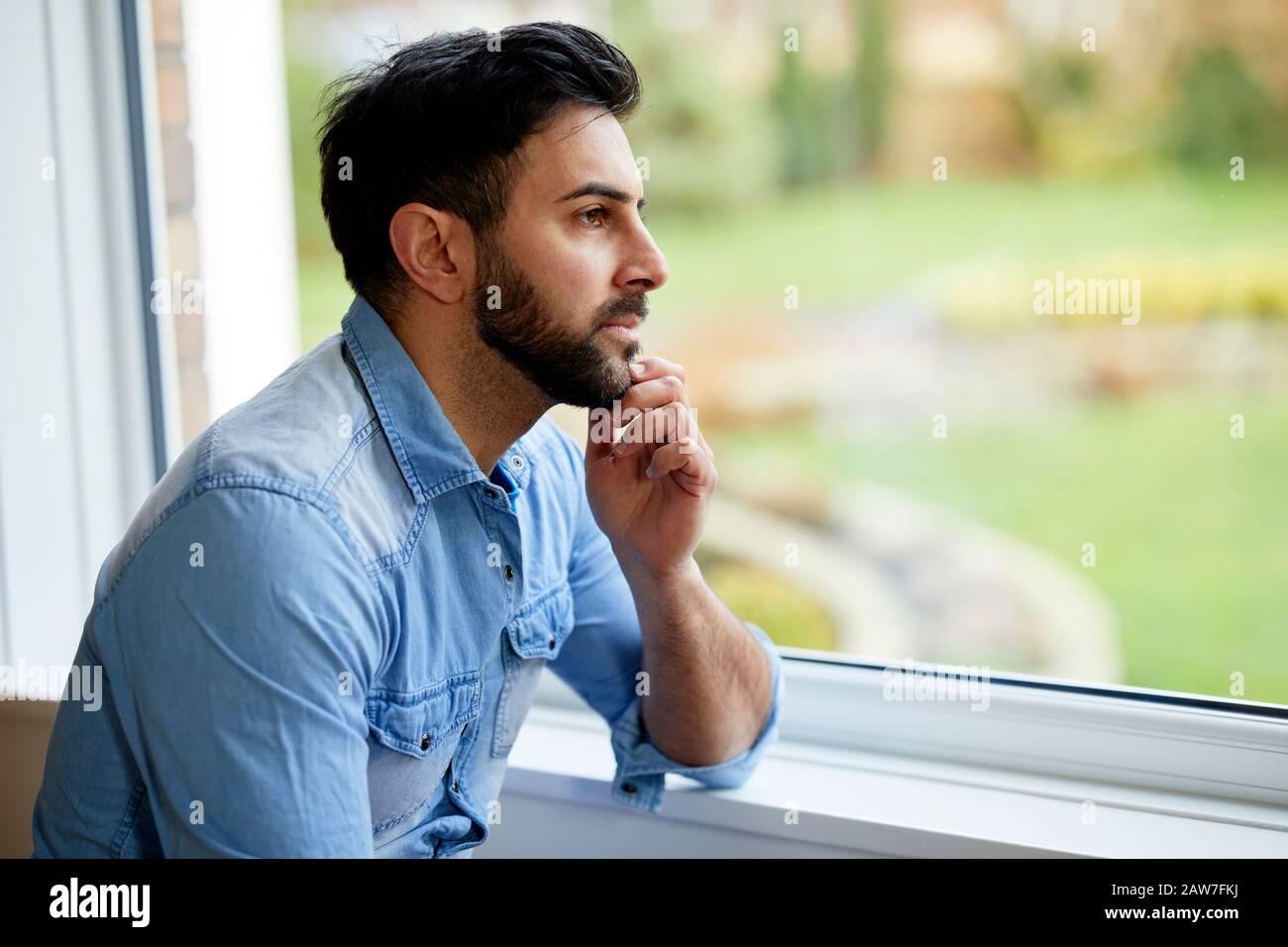 Uomo che guarda fuori della finestra Foto Stock
