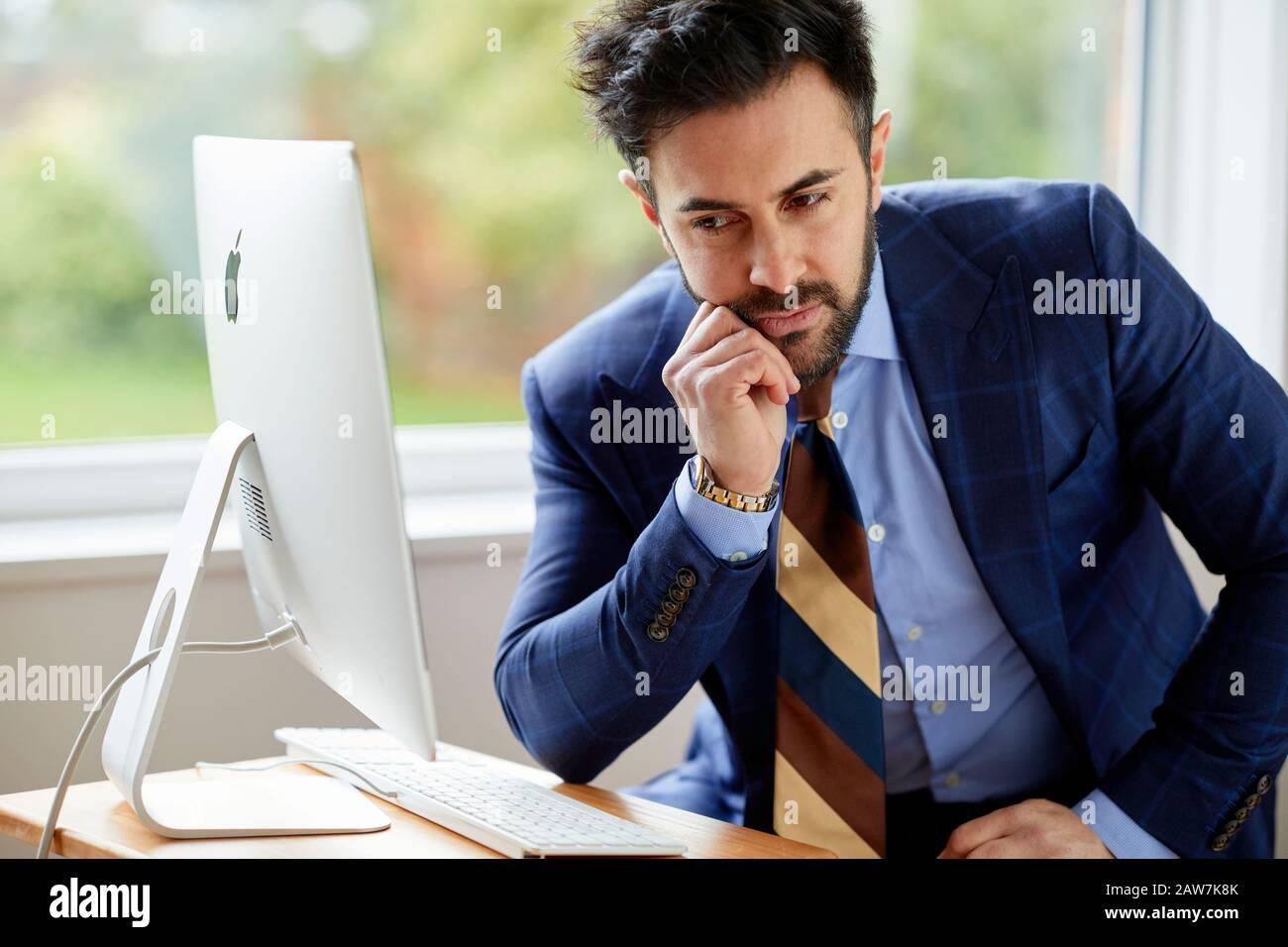 Uomo seduto al computer pensieroso Foto Stock