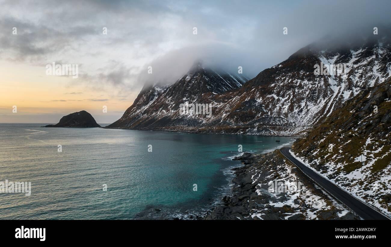 Bellissima spiaggia dietro il circolo polare nell'isola di lofoten a nord della norvegia che si affaccia sul tramonto. Spiaggia con acqua turchese e montagne mozzafiato sullo sfondo Foto Stock