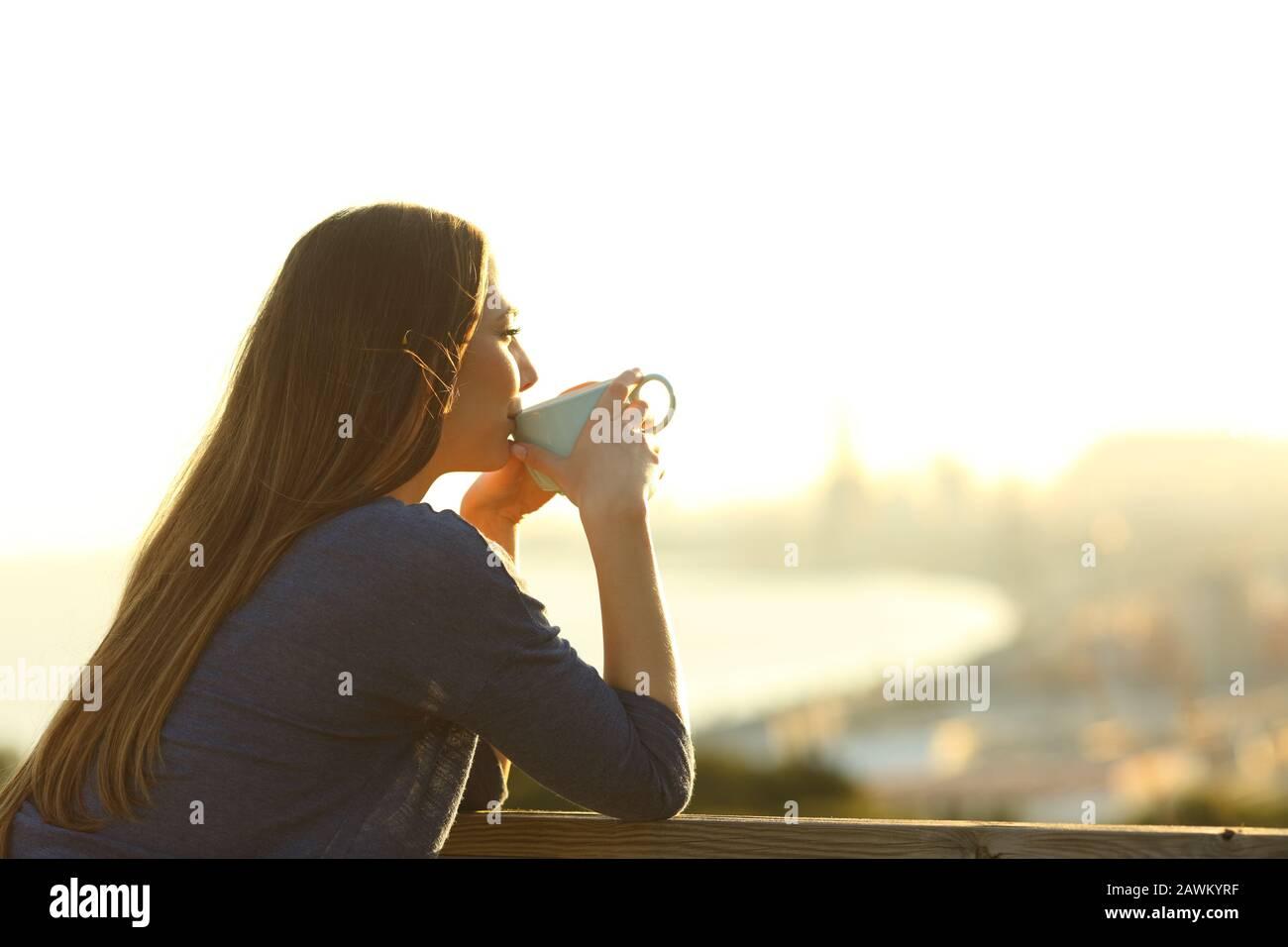 La ragazza felice beve caffè contemplando le viste da un balcone al tramonto Foto Stock