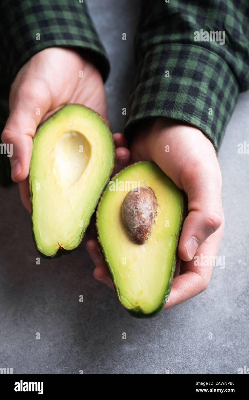 Mani maschili che tengono metà avocado. Alimentazione sana, stile di vita sano, concetto di dieta vegetariana Foto Stock