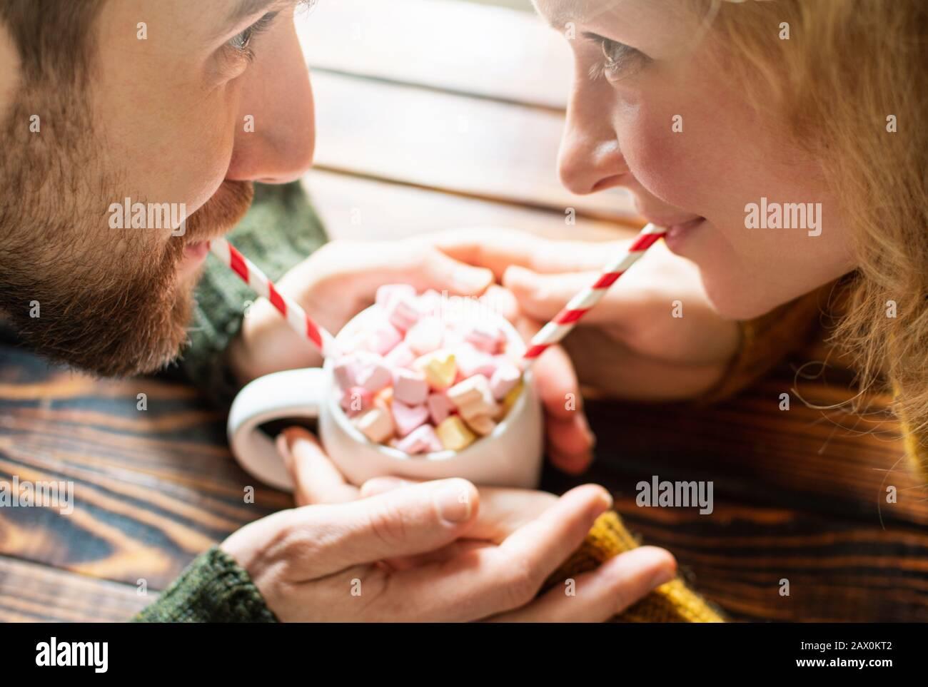 Giovane coppia bevendo cioccolata calda con marshmallows a forma di cuore usando cannucce da bere di carta. Data di San Valentino Foto Stock