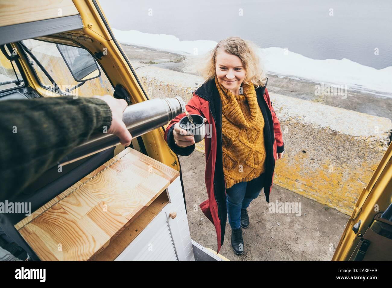 Giovane donna bionda accanto al camper che si affaccia sul mare invernale ghiacciato. Vista attraverso lo sportello aperto. Foto Stock