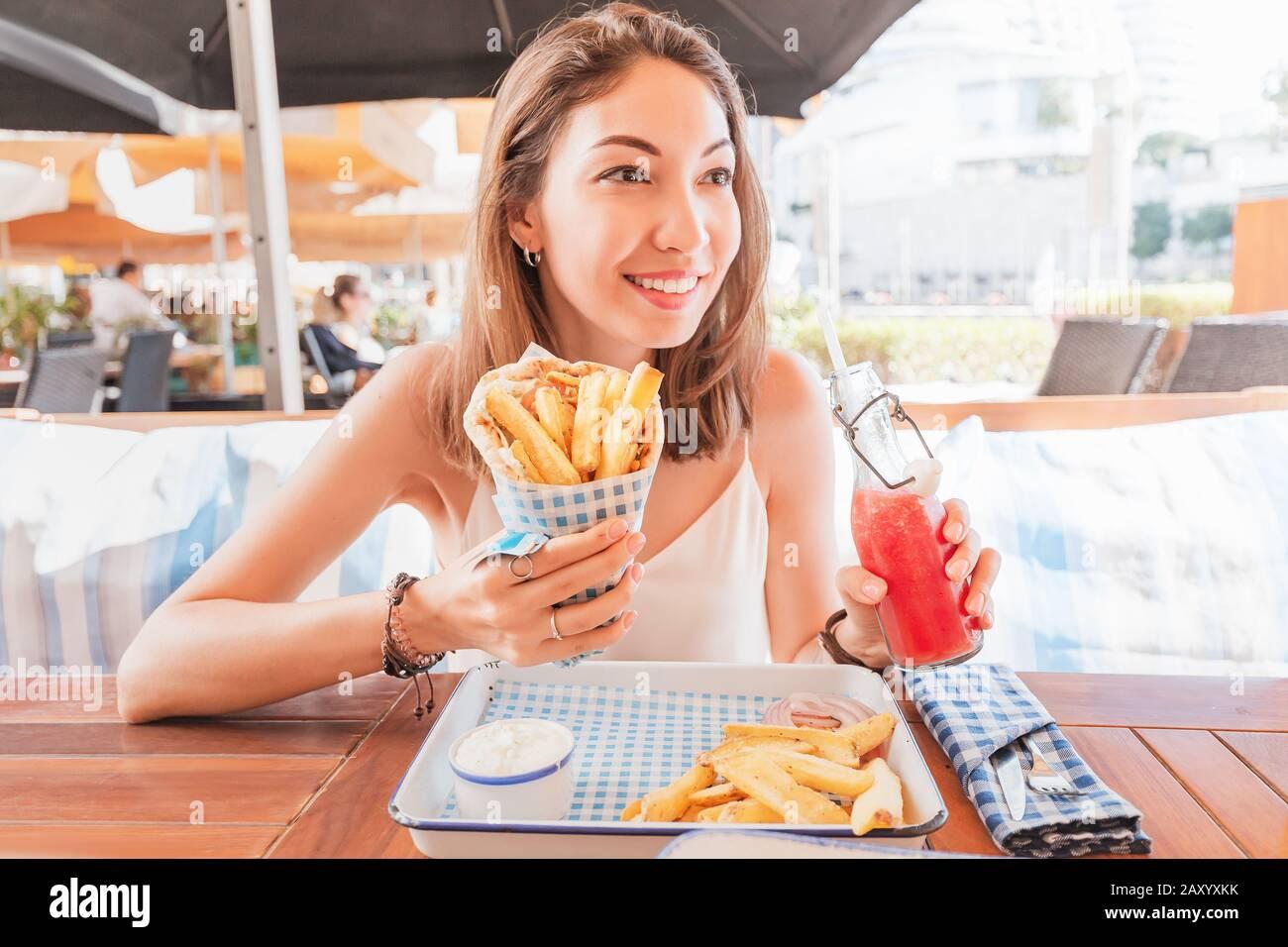 ragazza in street food caffè mangia gustosi e succosa giros con pita. Concetto di cucina mediorientale Foto Stock