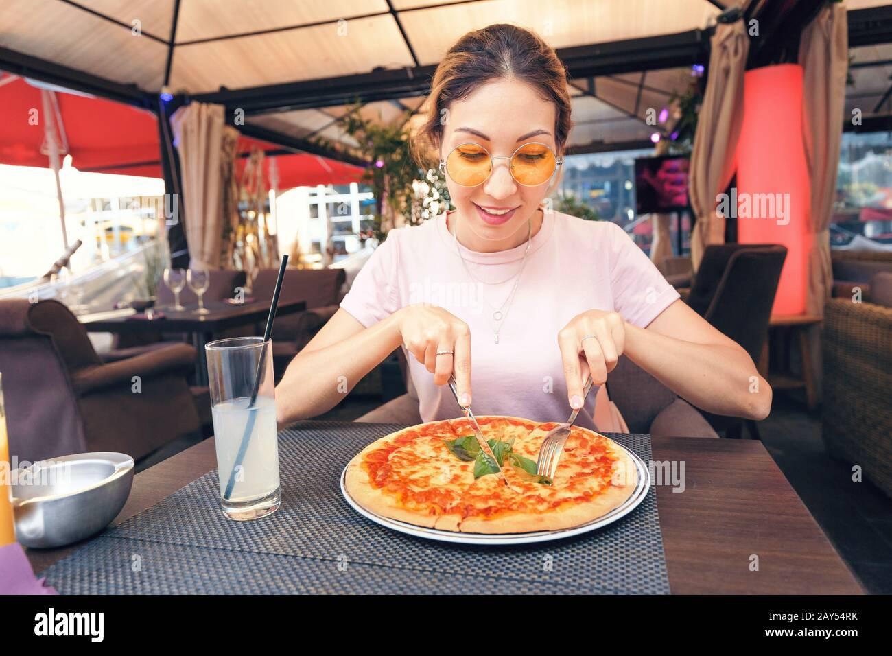 Giovane ragazza che mangia deliziosa pizza con formaggio e verdure in pizzeria Foto Stock