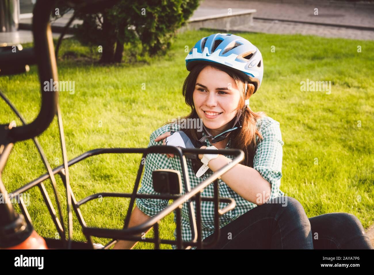 Ciclista femminile in abbigliamento professionale da ciclismo e casco seduto vicino alla bicicletta, godendosi il sole. Relax prendendosi il riposo. Vita sana Foto Stock