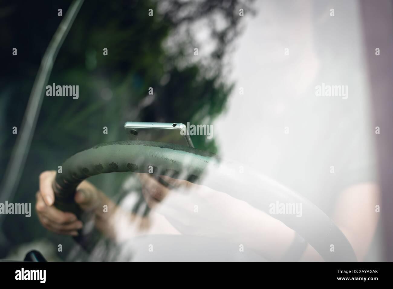 donna che usa lo smartphone in auto Foto Stock