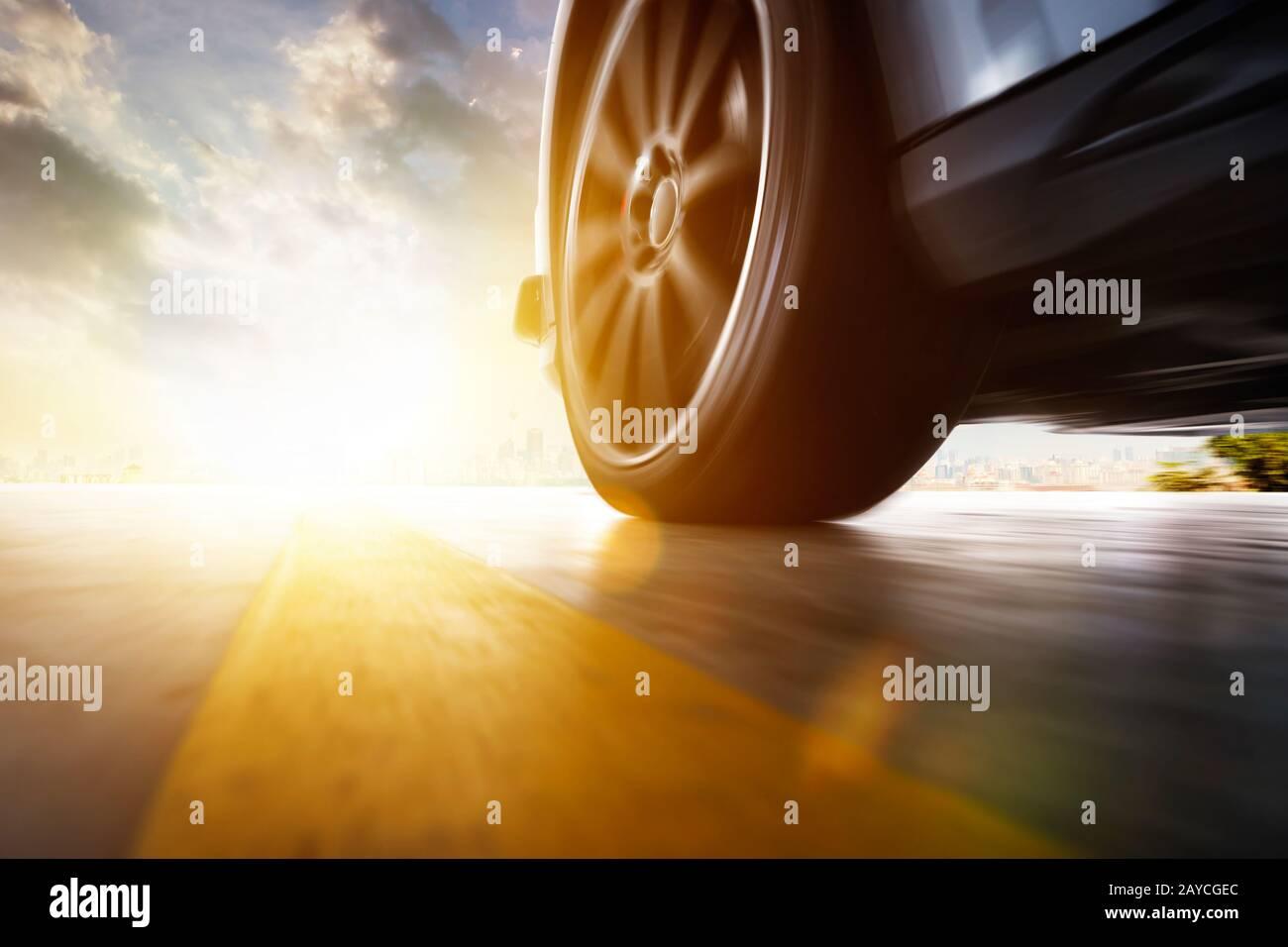 Basso angolo vista laterale di guida auto veloce al tramonto con la velocità di spostamento per effetto . Foto Stock