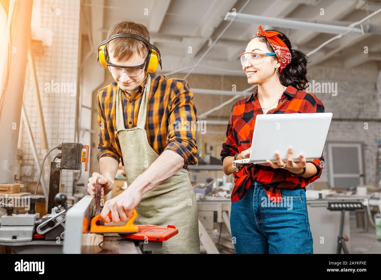 Donna asiatica con un laptop e un uomo con una sega circolare che lavora in una fabbrica o in un laboratorio Foto Stock