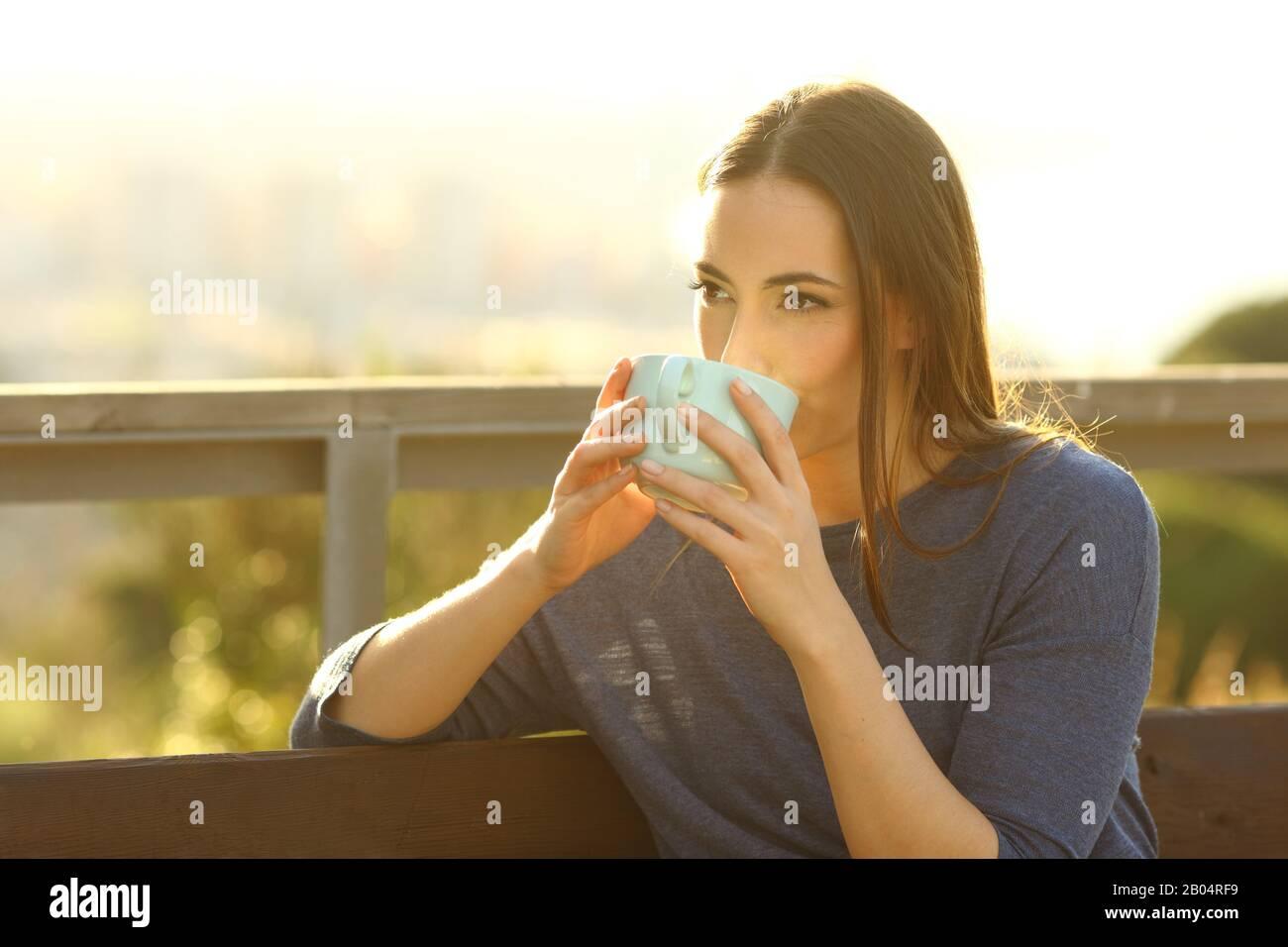 Donna rilassata bevendo caffè seduto su una panchina in un parco al tramonto Foto Stock