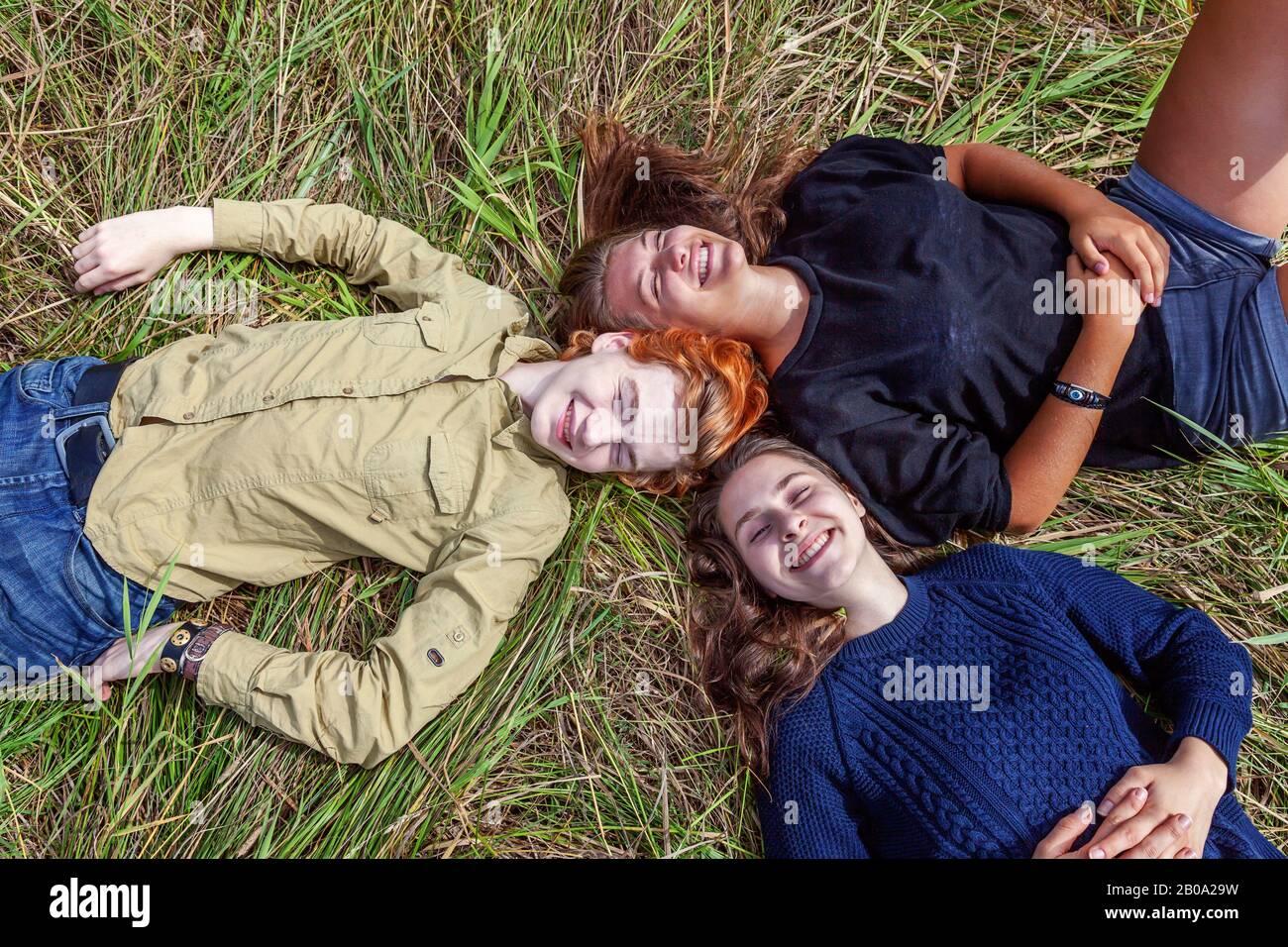 Vacanze estive vacanza felice persone concetto. Vista dall'alto gruppo di tre amici che si trovano sull'erba in cerchio sorridendo e divertirsi insieme all'aperto. Picnic con gli amici in viaggio in natura Foto Stock
