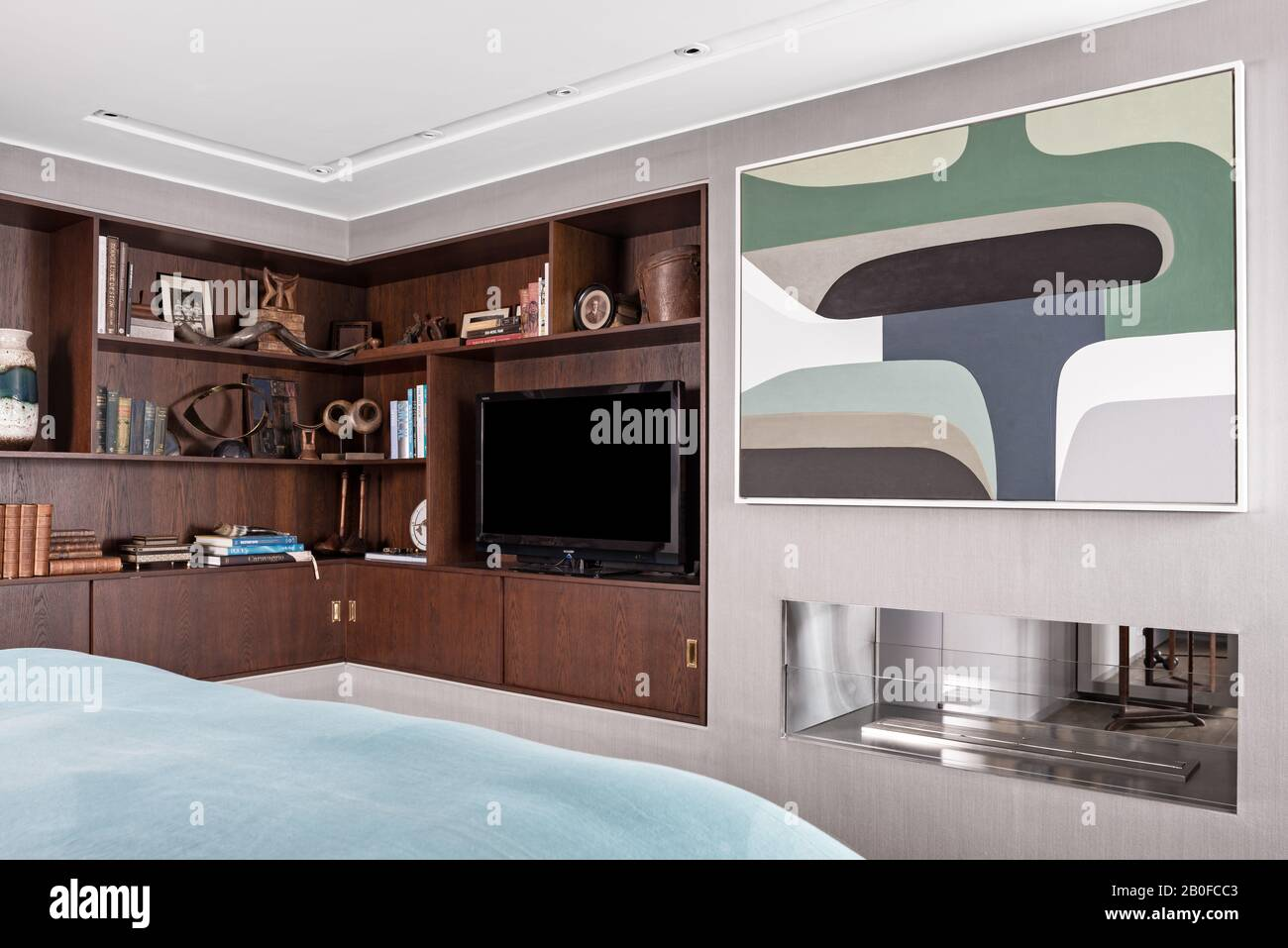 TV su scaffalature rivestite in legno e grandi opere d'arte nella camera da letto del moderno appartamento West London. Foto Stock