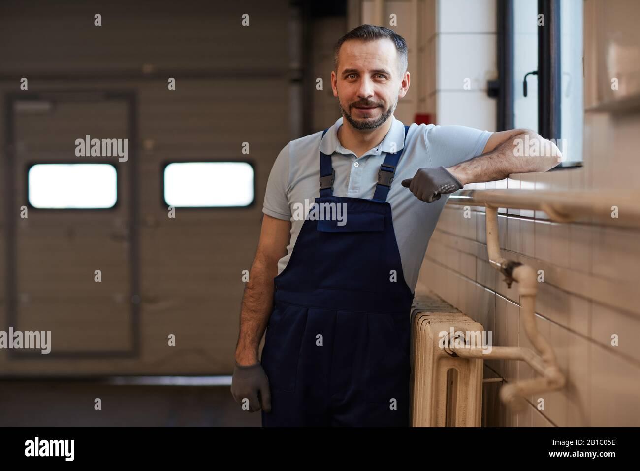 Girovita ritratto di macchina matura meccanico appoggiato a parete mentre posa in officina riparazione auto, copia spazio Foto Stock