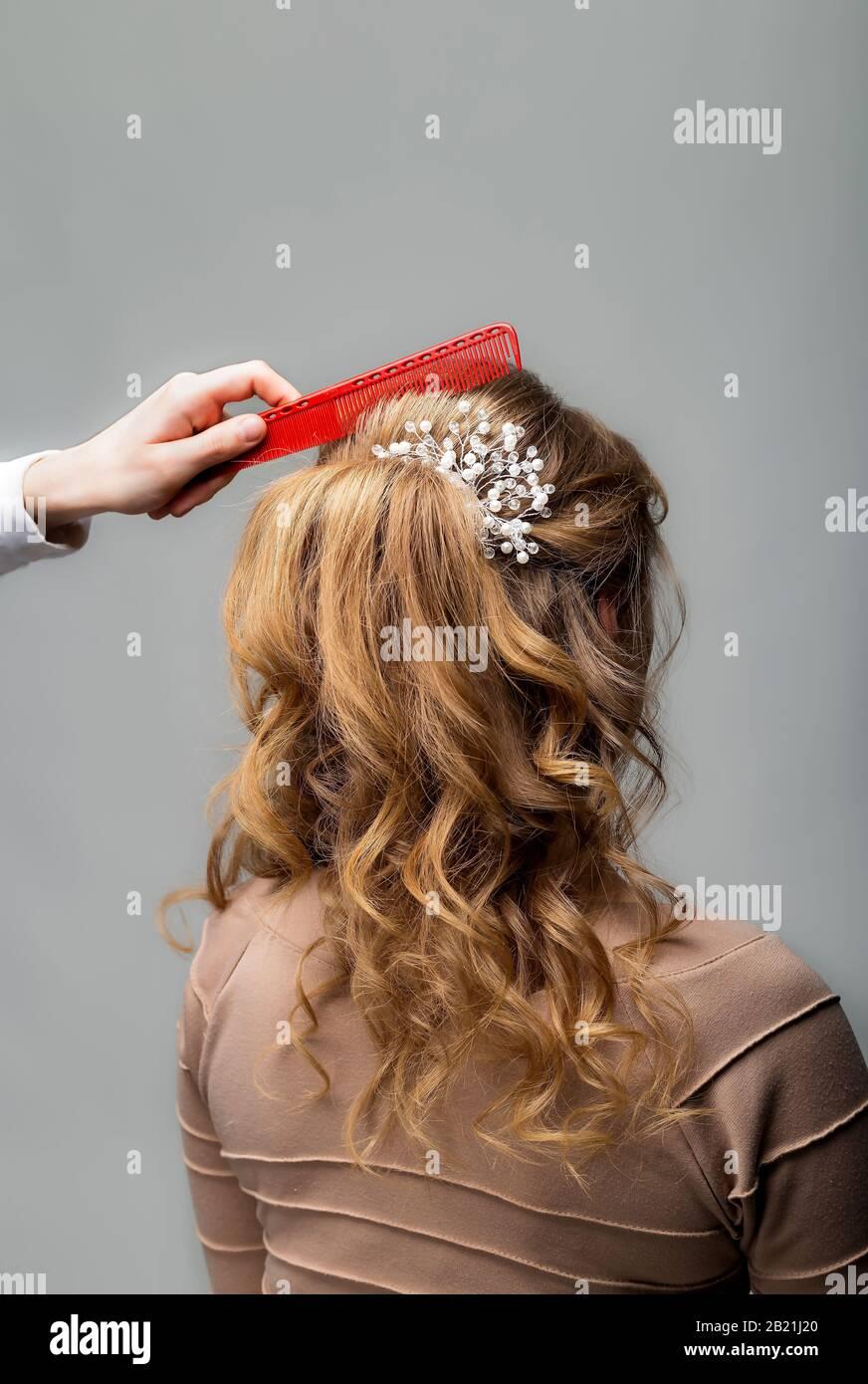 Capelli ricci ondulati. Parrucchiere che fa acconciatura a donna bionda capelli con capelli lunghi utilizzando il pettine su sfondo grigio. Parrucchiere professionale Foto Stock