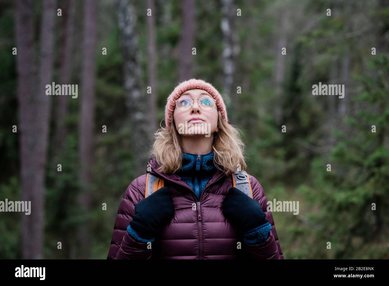 ritratto di una donna che guarda il cielo in una foresta in inverno Foto Stock