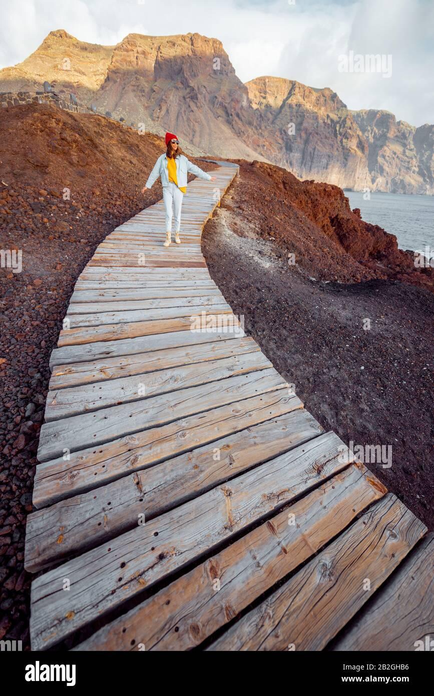 Donna che cammina sul pittoresco sentiero in legno attraverso la terra rocciosa con le montagne sullo sfondo. Viaggiando sul capo nord-ovest dell'isola di Tenerife, Spagna Foto Stock