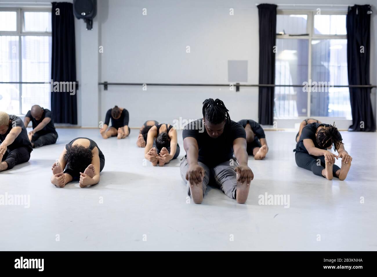 Ballerini moderni di razza mista che si allungano in uno studio Foto Stock