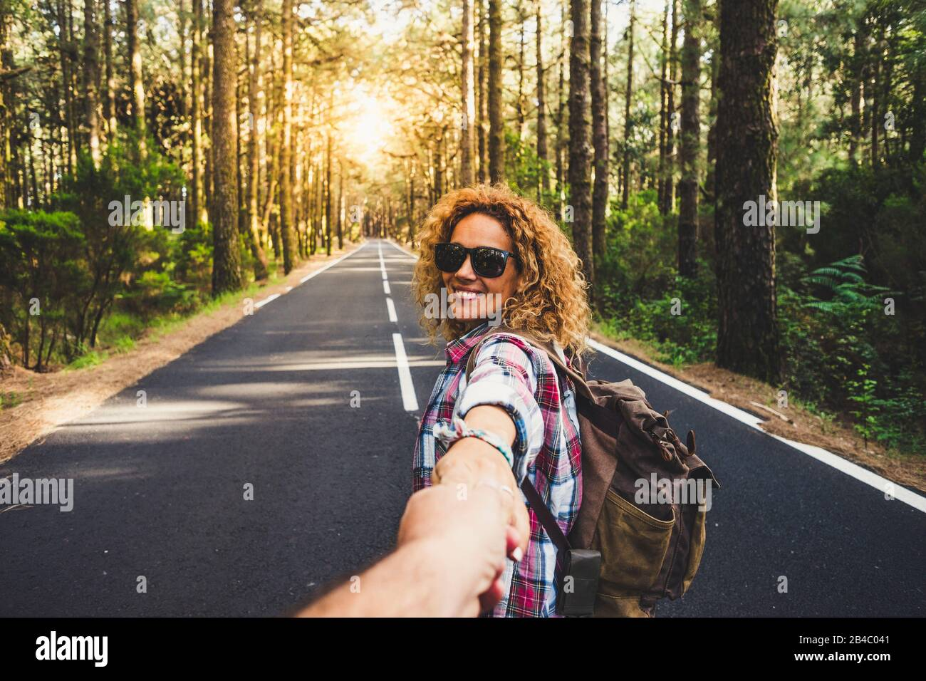 Coppie viaggiatori uomo e donna seguono le mani di tenuta a lungo strada foresta paesaggio e sole sullo sfondo Amore e Viaggi emozioni felici stile di vita concetto. Persone che viaggiano avventure attive vacanze Foto Stock