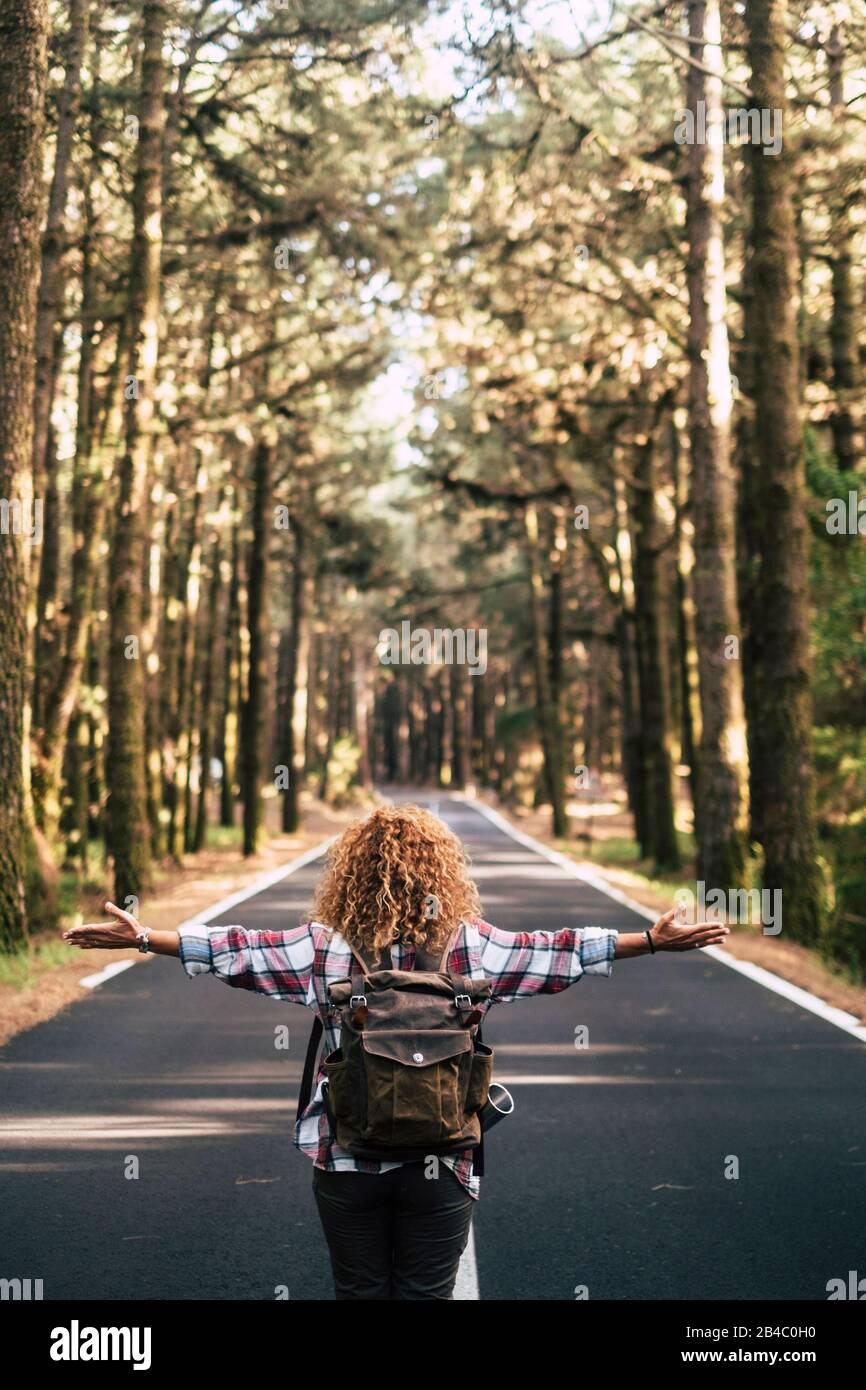 Concetto di viaggio alternativo con la donna maledetta hipster vista dalla schiena aprire le braccia e sentire la libertà della natura all'aperto in piedi nel mezzo di una strada in mezzo alla ling - felicità e wanderlust stile di vita Foto Stock
