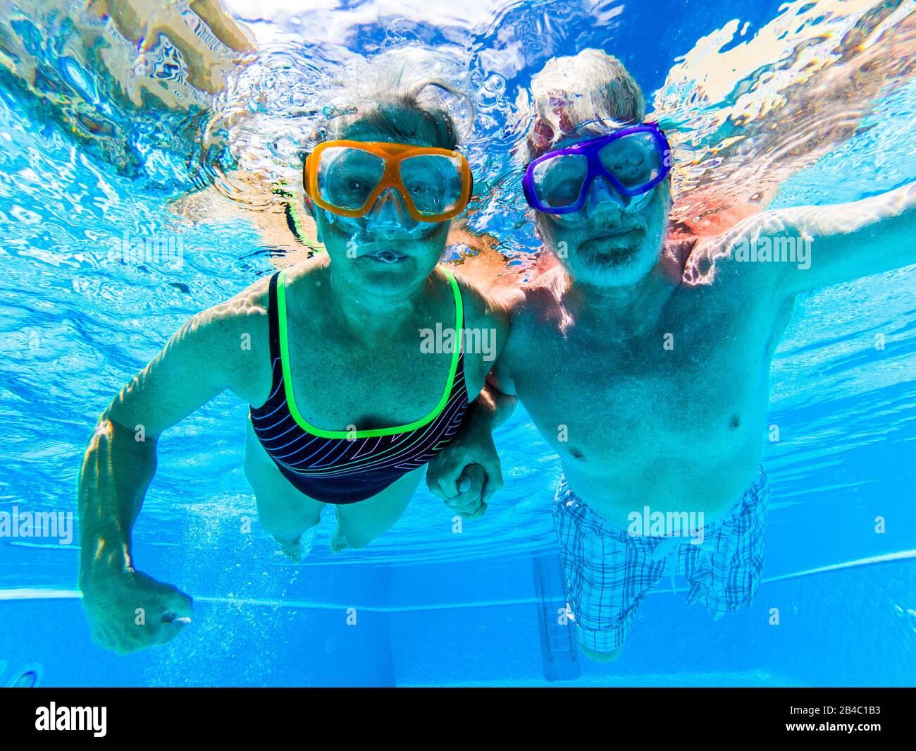 Adulti persone senior coppia divertirsi nuotate in piscina sott'acqua con colorate maschere divertenti immersione - concetto di immersione e attivo pensionati uomo e donna godendo lo stile di vita - acqua blu e adulti caucasici Foto Stock