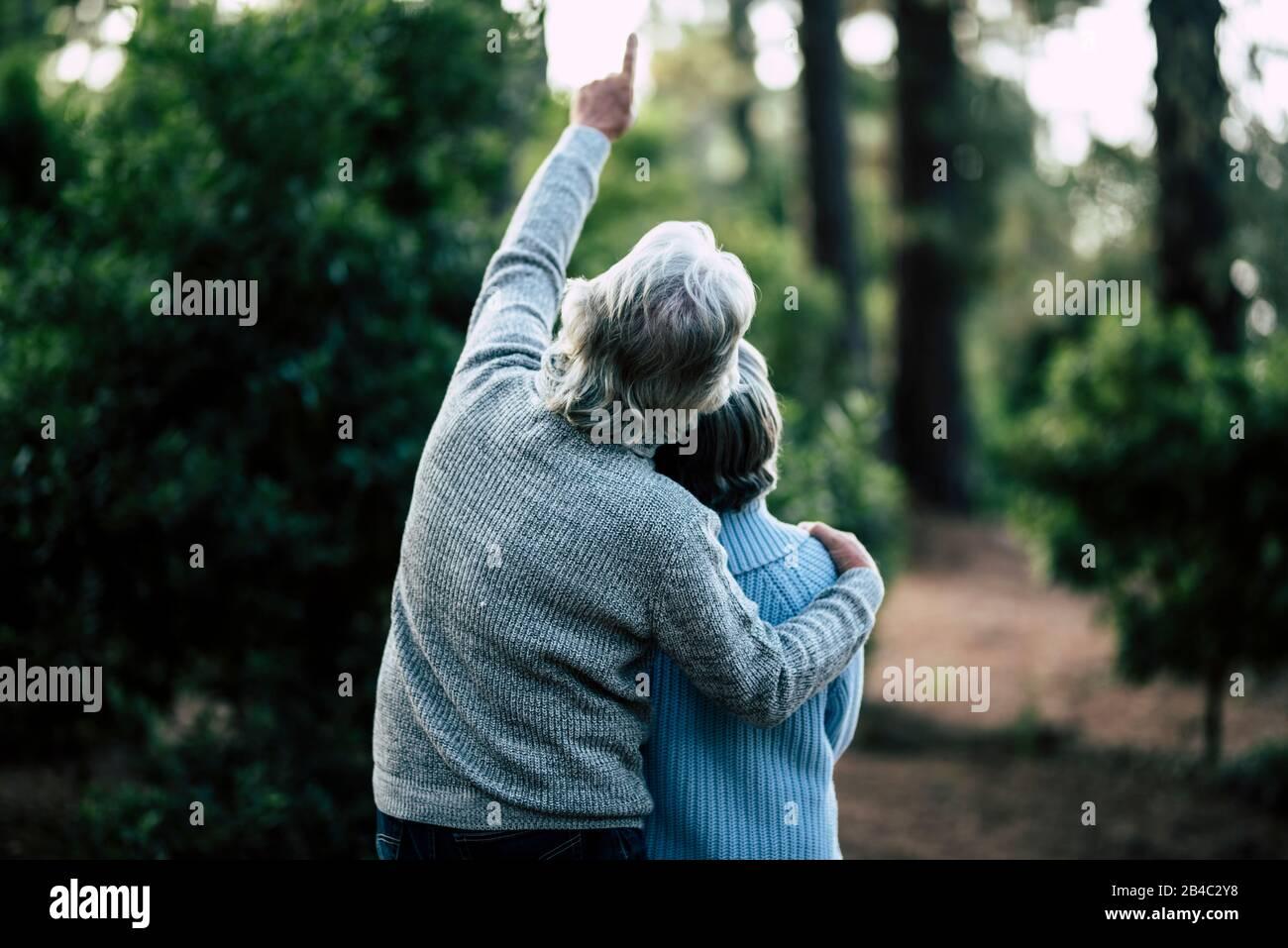 Coppia di anziani maturi abbracciano e godono l'attività di svago all'aperto insieme nella foresta - alberi verdi sullo sfondo - uomo irriconoscibile e donna per anziani sano ilstile Foto Stock