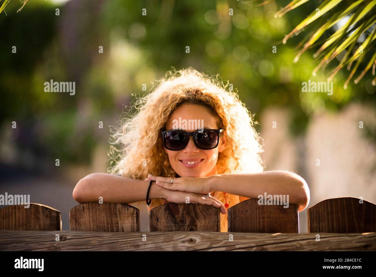 Ritratto di bella caucasica giovane bionda curly donna allegro guardando la fotocamera con luci del sole in background e defocused verde naturale sfondo esterno - felice età media signora concetto Foto Stock