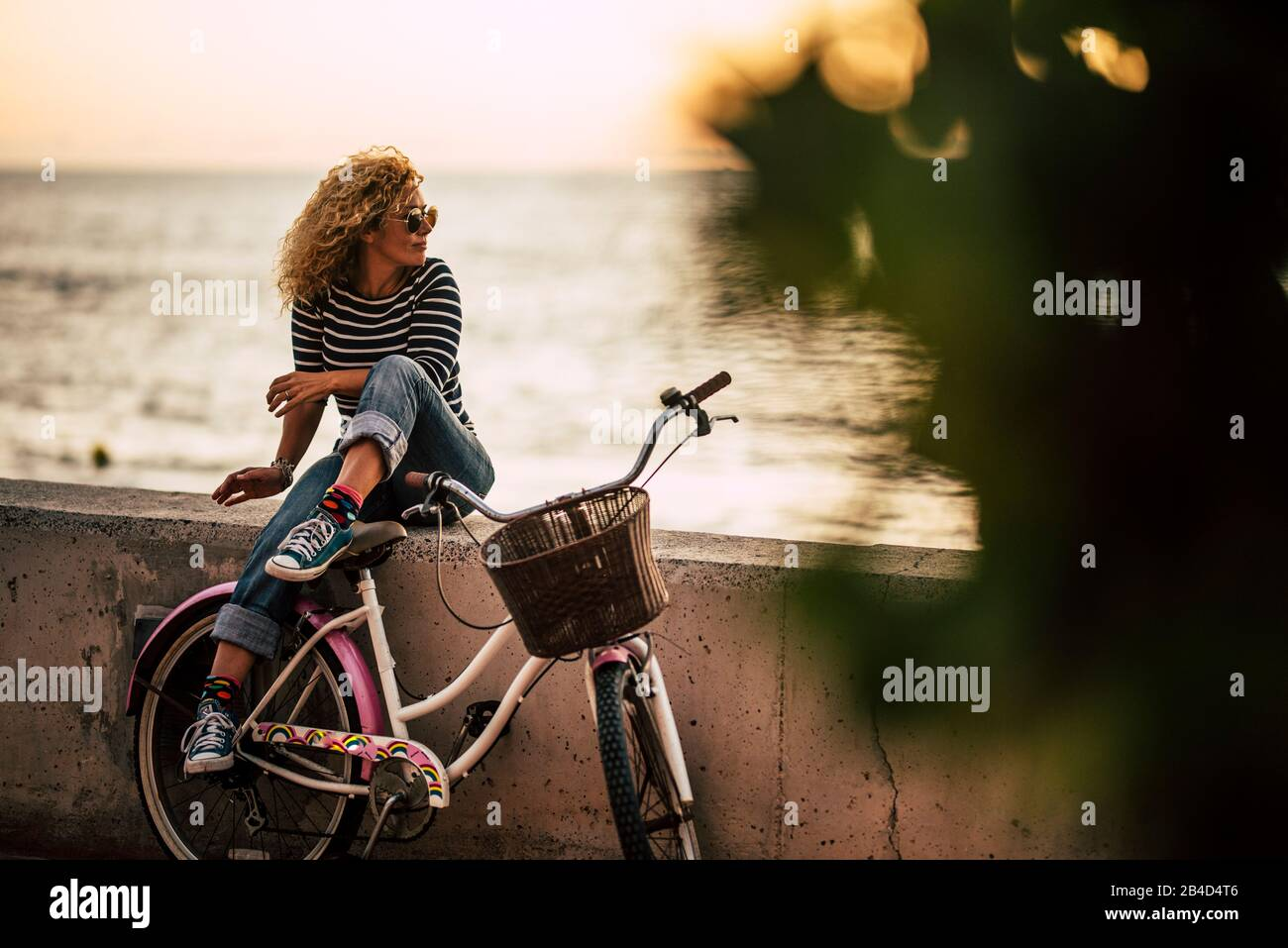 Donna caucasica adulta che gode di attività di svago all'aperto rilassante dopo un giro su una bicicletta d'epoca, seduta su un muro che guarda l'oceano - persone sane e attive lifestyle Foto Stock