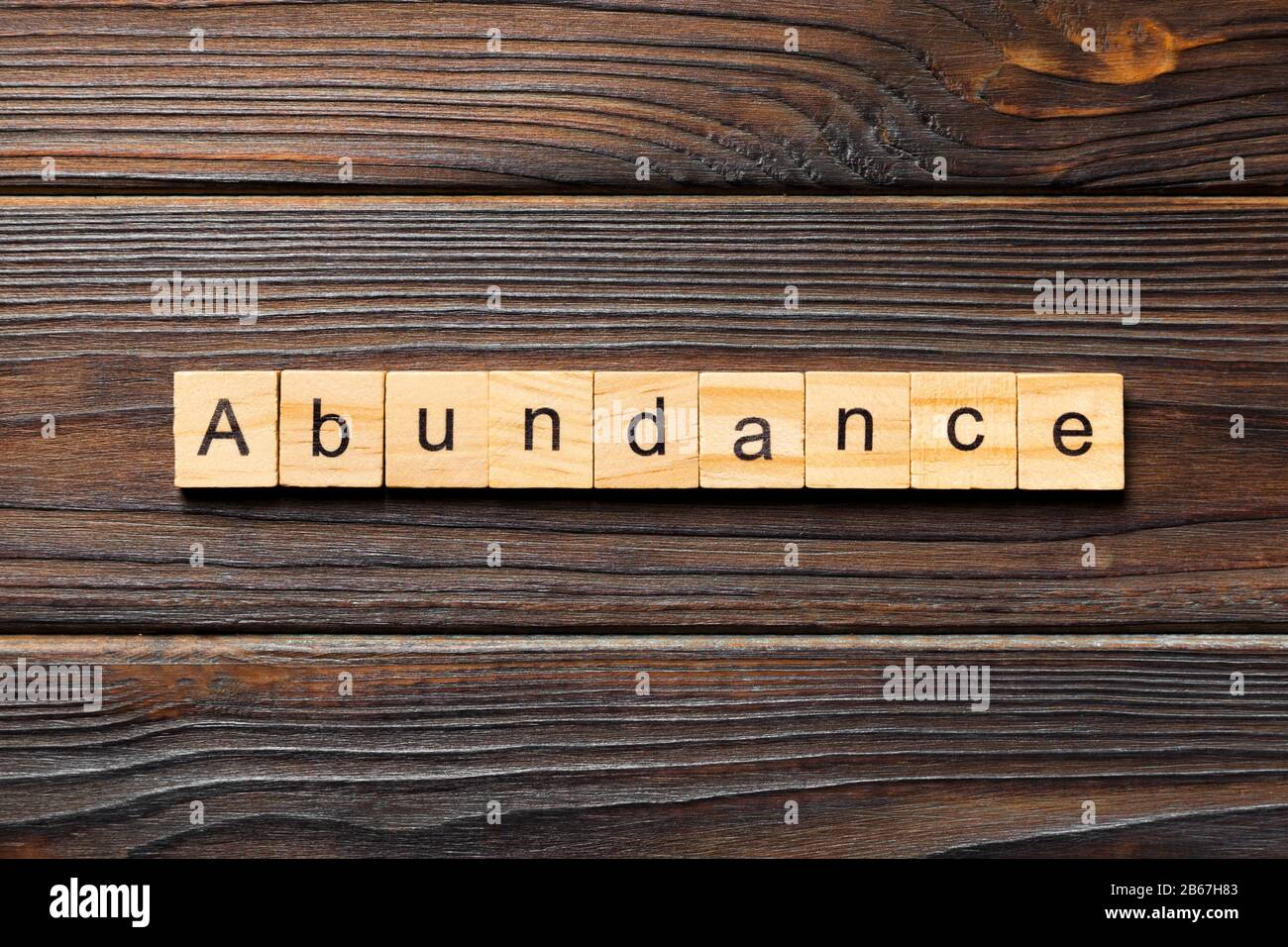 Parola di abbondanza scritta su blocco di legno. Abbondanza di testo su tavola di legno per il vostro concetto di desing, vista dall'alto. Foto Stock