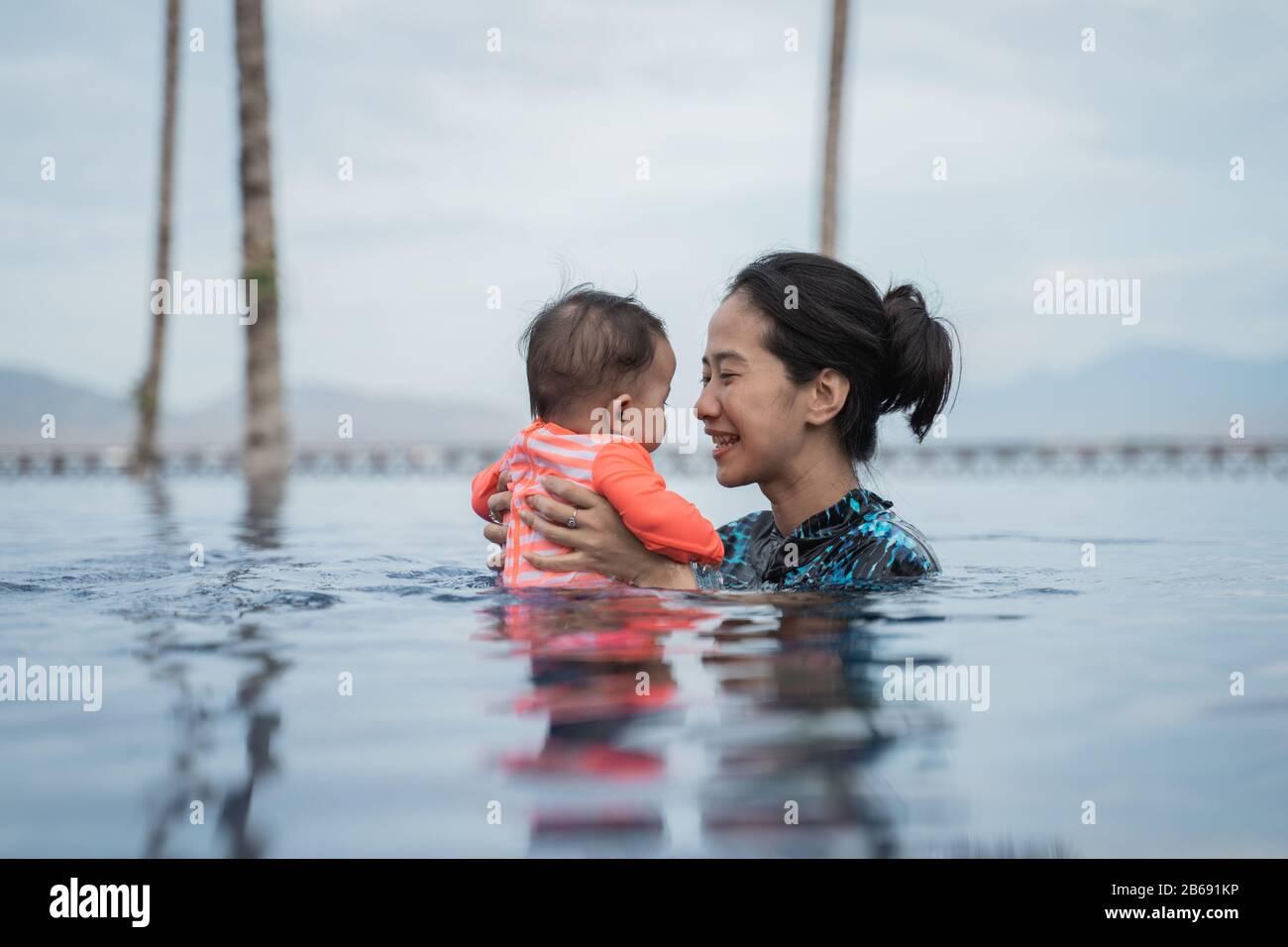 madre che tiene il suo bambino mentre nuotano nella piscina mentre godendo giocare insieme Foto Stock