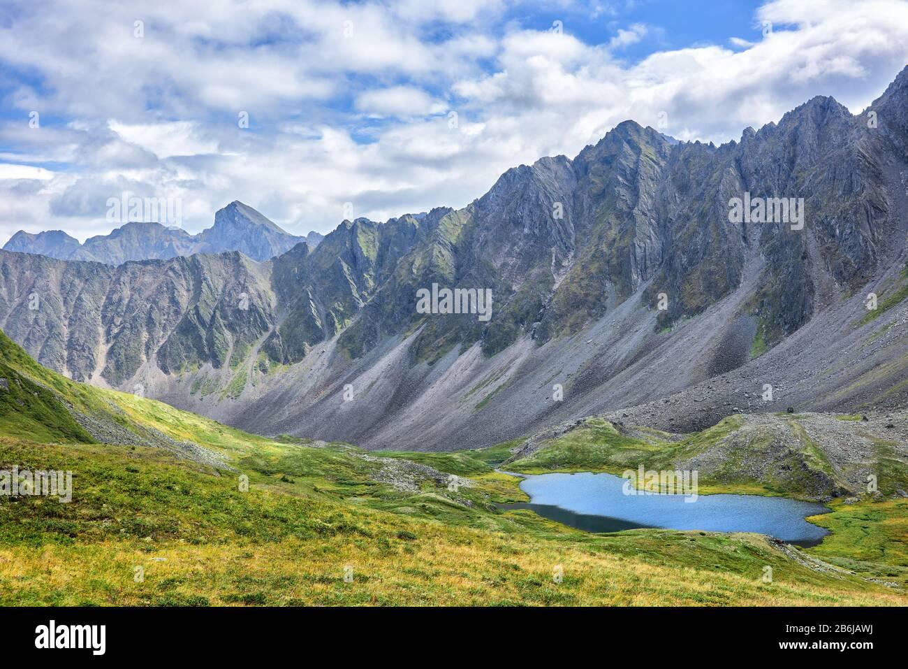 Tundra alpina siberiana sullo sfondo della catena montuosa. Un caratteristico paesaggio alpino con vegetazione scarsa nella Siberia orientale. Valle di valle Foto Stock