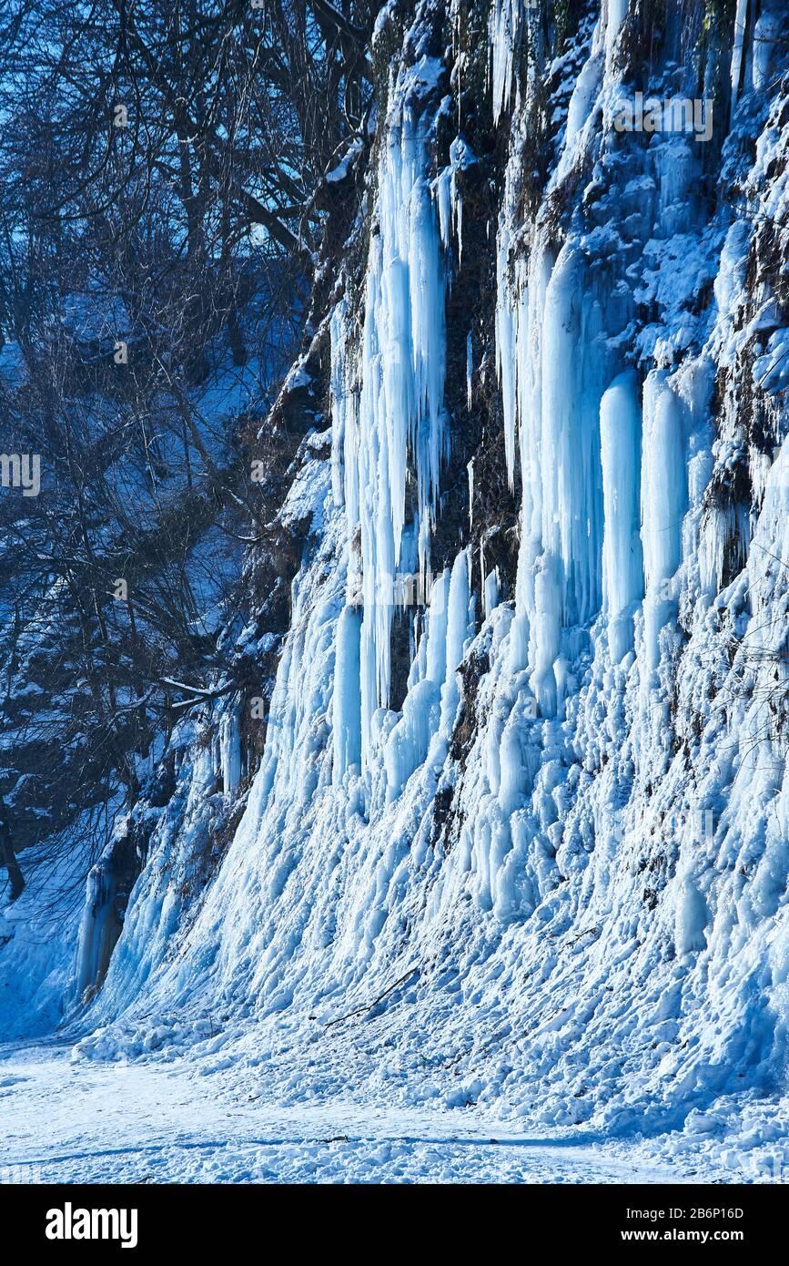 Grandi ghiaccioli pendono dalla banca del fiume cliff. Foto Stock
