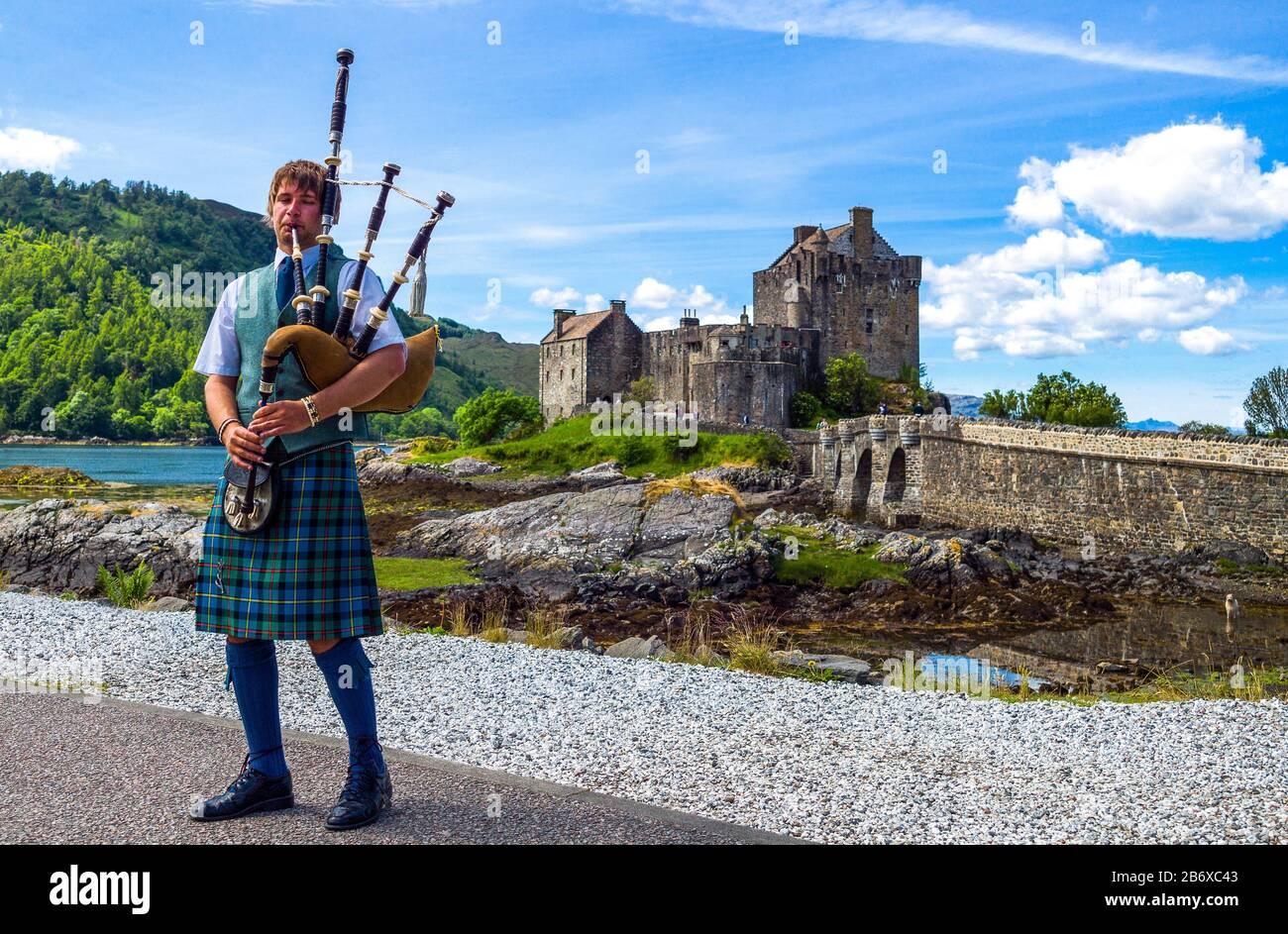 Lochash, Scozia, Highlands, un giocatore di cornamusa e il castello di Eilean Donan sullo sfondo Foto Stock